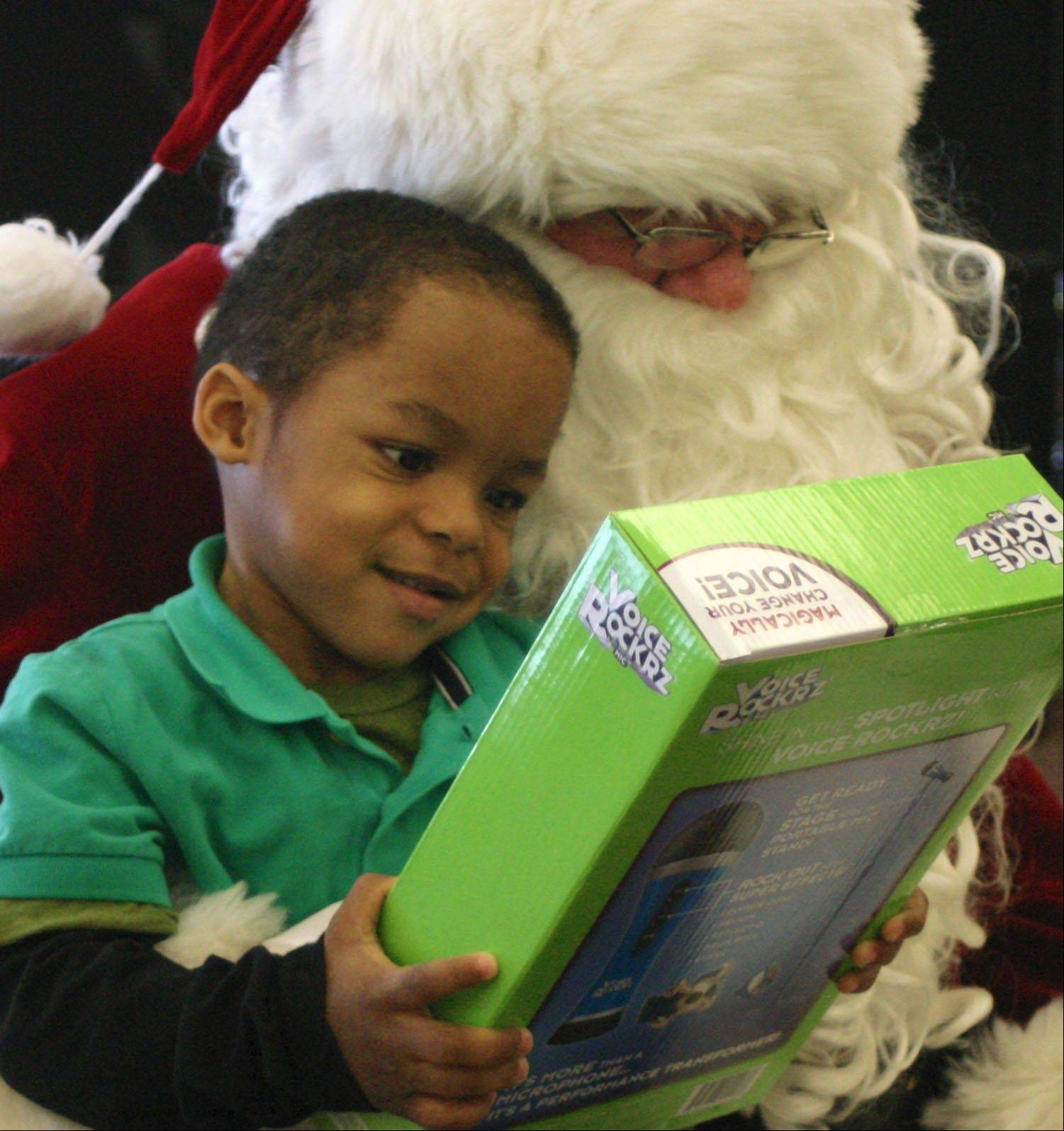 Mooseheart preschool student Cedan Echols is all smiles after receiving his gift from Santa Claus during Santa's annual visit to the school Dec. 19.