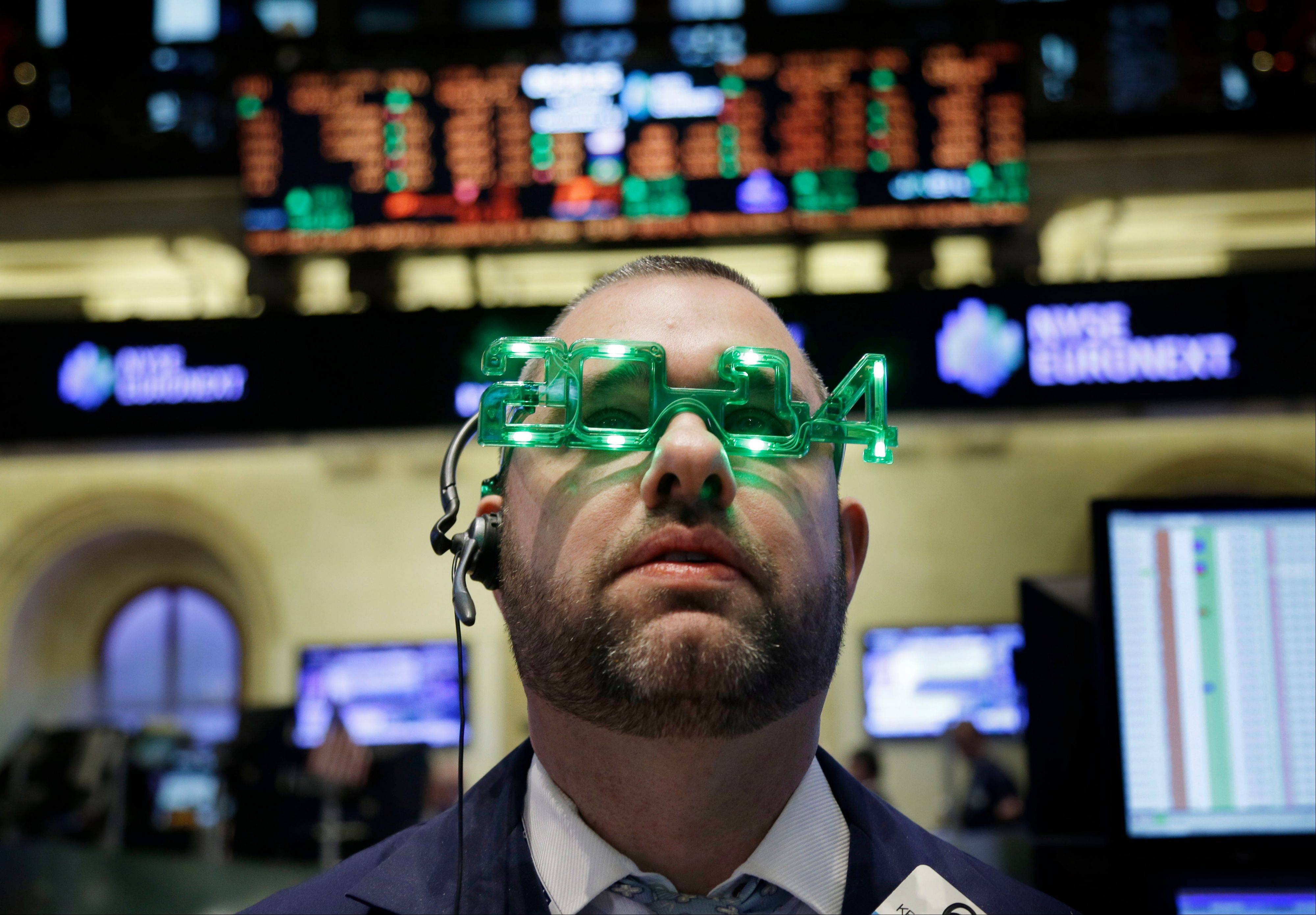 A trader wears glasses celebrating the new year while working on the floor at the New York Stock Exchange Tuesday. The Standard & Poor's 500 Index posted its biggest annual advance since 1997, as gains in consumer confidence and housing prices bolstered confidence in the world's largest economy.