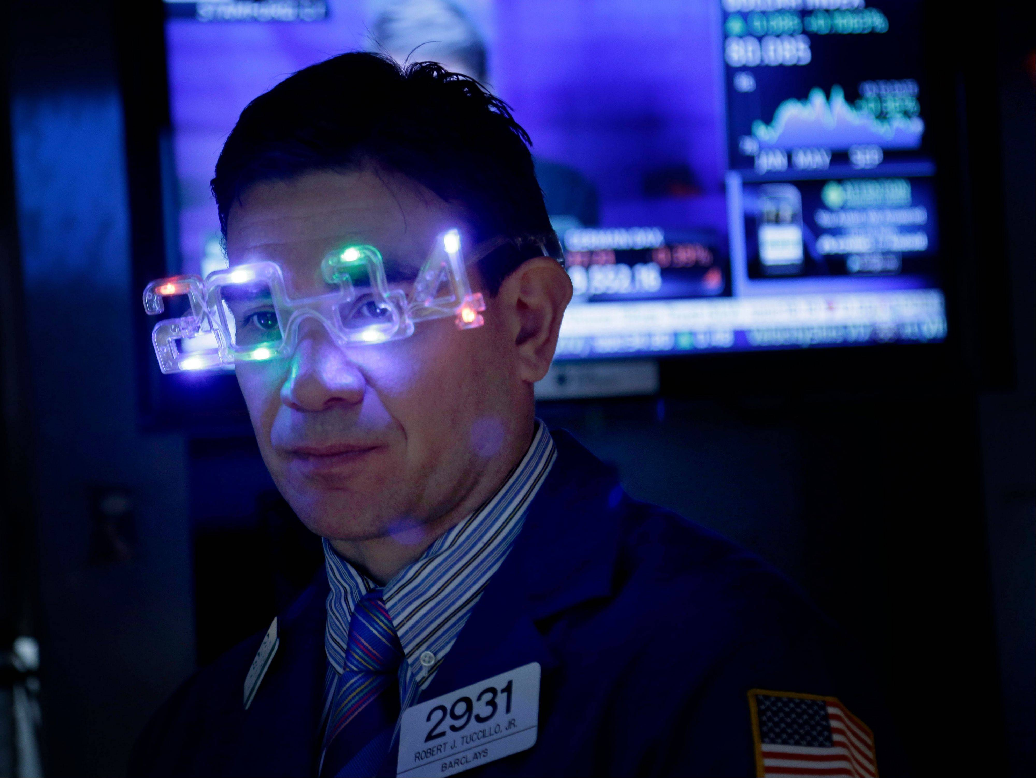 A trader wears glasses celebrating the new year while working on the floor at the New York Stock Exchange Tuesday. The Standard & Poor�s 500 Index posted its biggest annual advance since 1997, as gains in consumer confidence and housing prices bolstered confidence in the world�s largest economy.