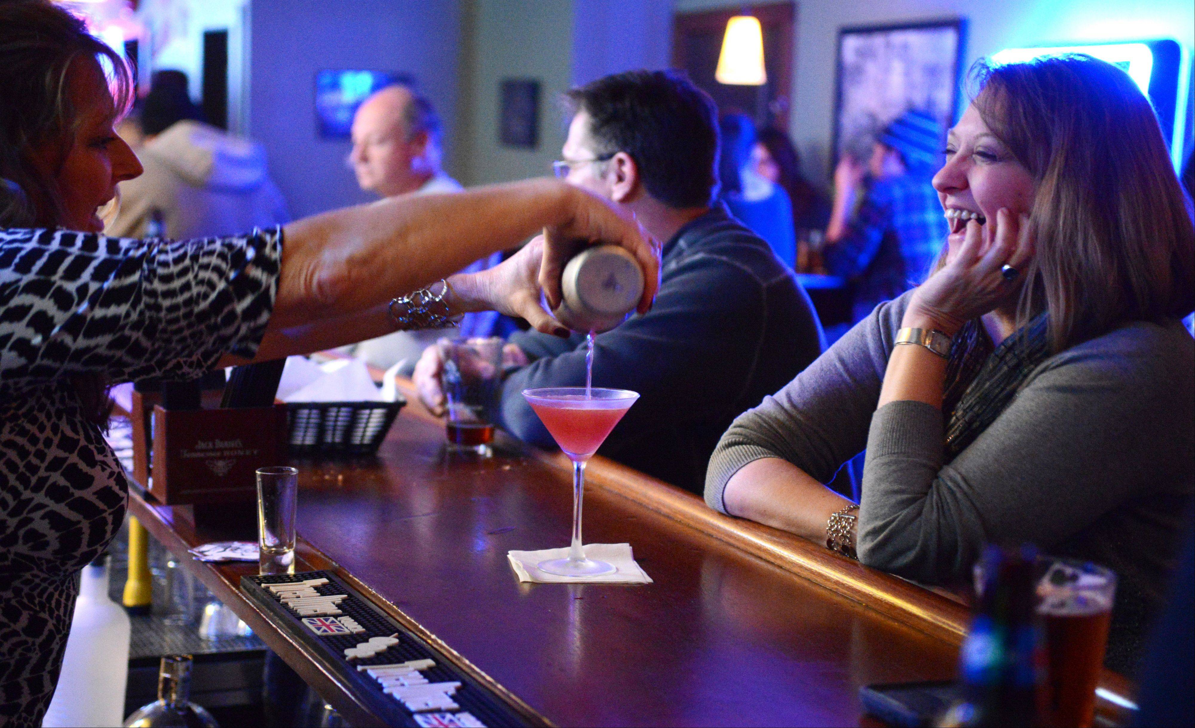 Bartender Mickey Phillip pours a cosmopolitan for Jennifer Vick of Batavia at Wilson Street Tavern.