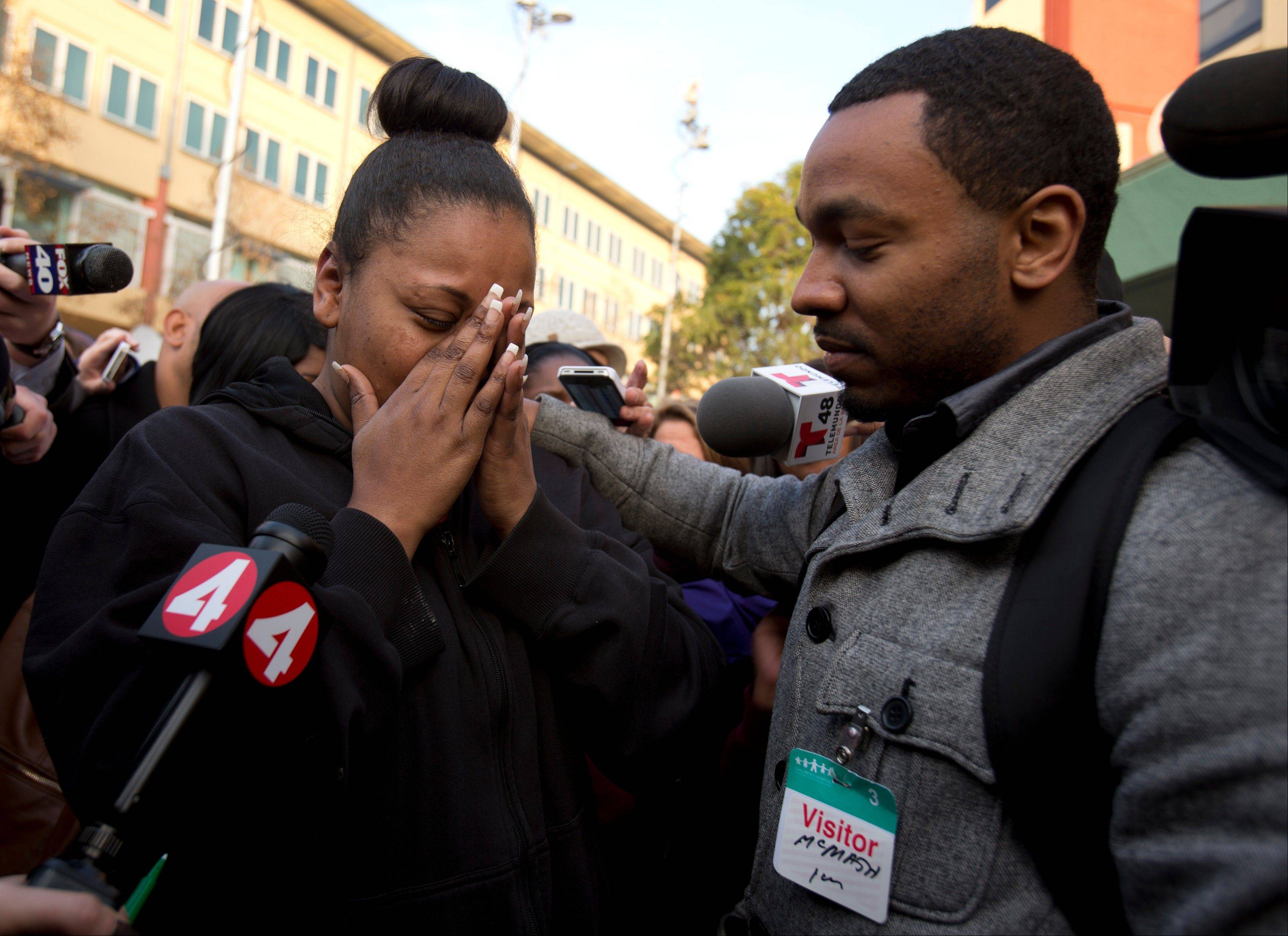 Nailah Winkfield, left, mother of 13-year-old Jahi McMath, is comforted by brother Omari Sealey as she talks to the media outside Children's Hospital Oakland, Monday in Oakland, Calif. McMath, who was declared brain dead after complications of a tonsillectomy, will now stay on a ventilator through Jan. 7.