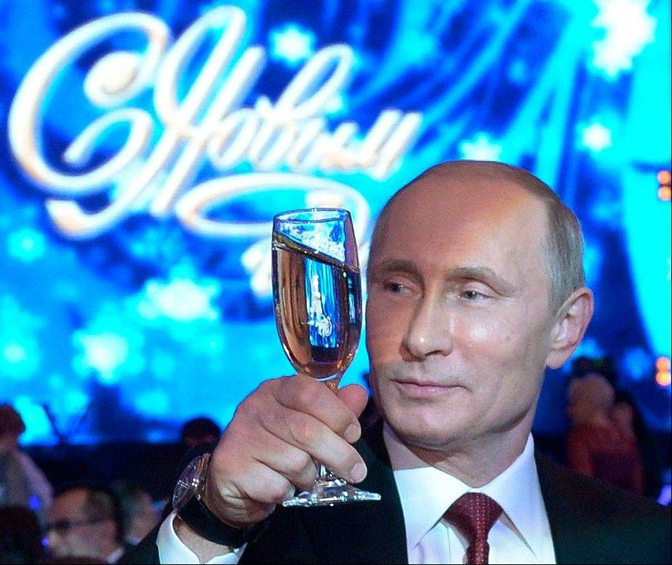 "ASSOCIATED PRESS Russian President Vladimir Putin, toasts during a New Year dinner in Khabarovsk, Russia's Far East, Tuesday, with a neon sign behind declaring ""Happy New Year."""