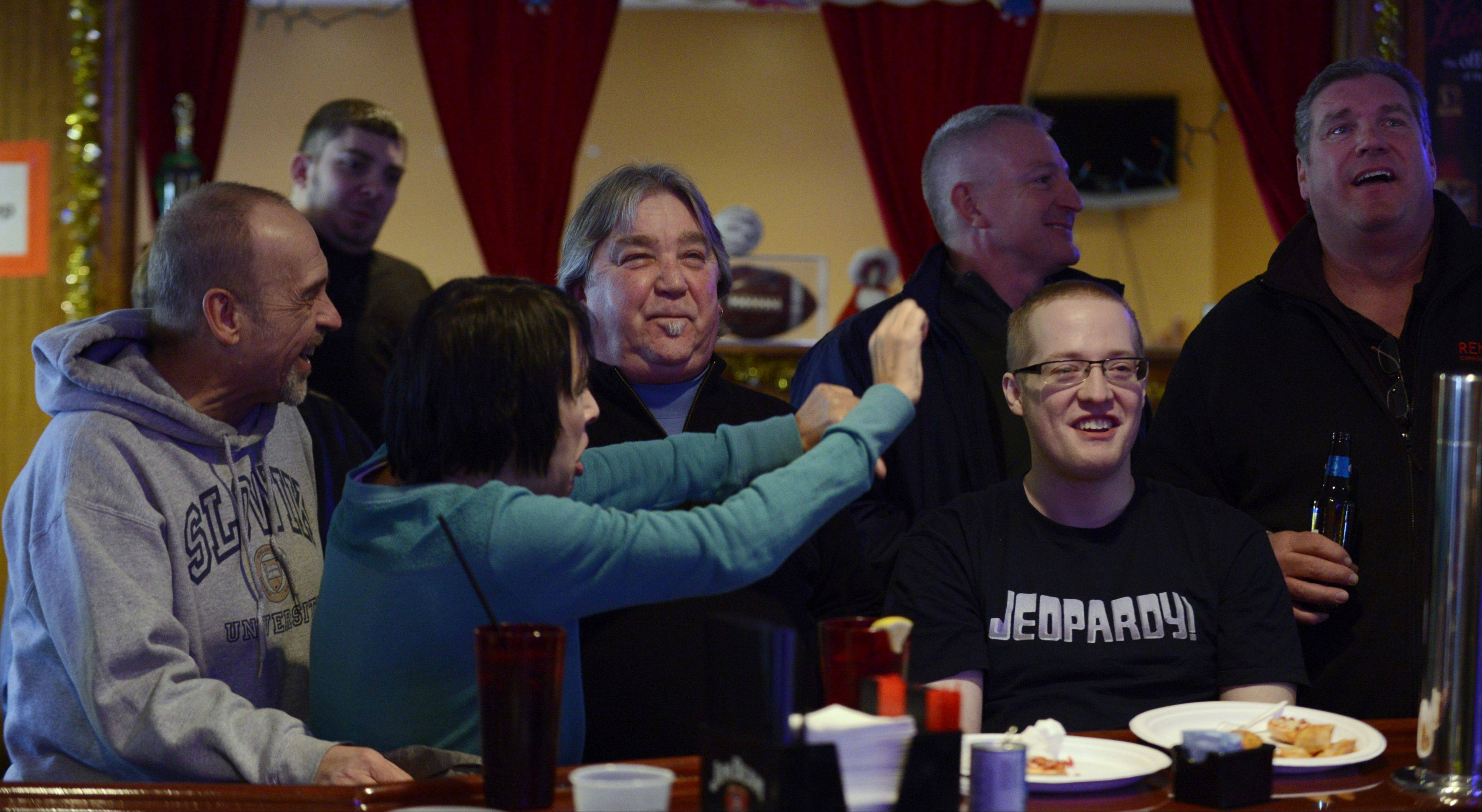 "Though he did win and his run will continue at least one more show, Jerry Slowik of Arlington Heights, front right, takes some gentle teasing from his dad, Jerry, left, and mom, Debbie, after missing a question on his ""Jeopardy!"" appearance. He watched his latest appearance on the program with friends New Year's Eve at Eddie's Restaurant and Lounge in Arlington Heights."