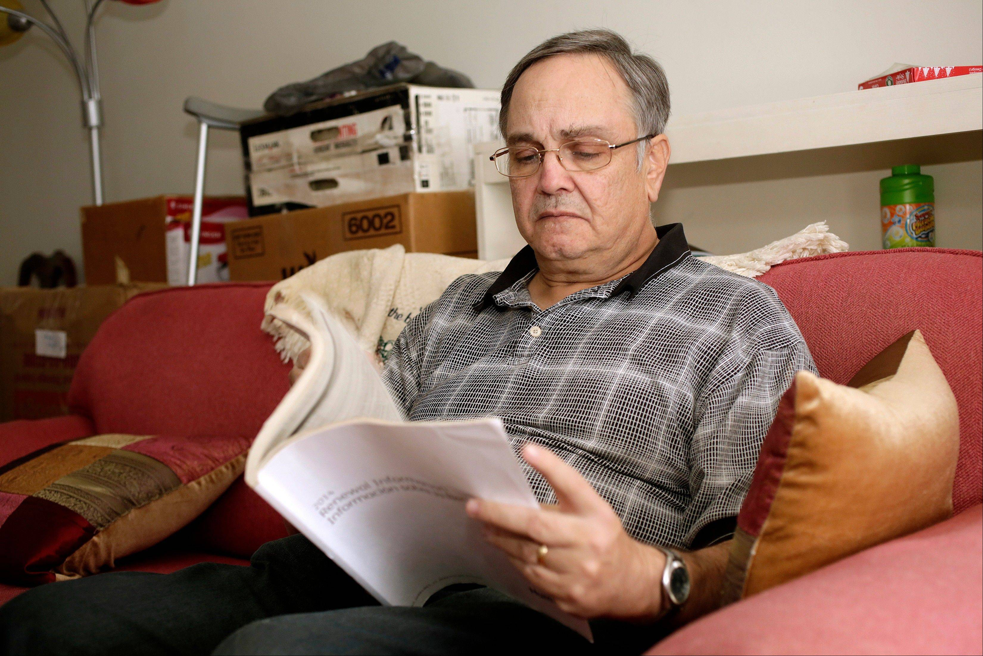 "Howard Kraft looks over healthcare information in his Lincolnton, N.C. home Monday. A painful spinal problem left him unable to work as a hotel bellman. But he's got coverage because federal law now forbids insurers from turning away people with health problems. ""I am not one of these people getting a policy because I'm being made to,"" Kraft said. ""I need one to stay alive."""