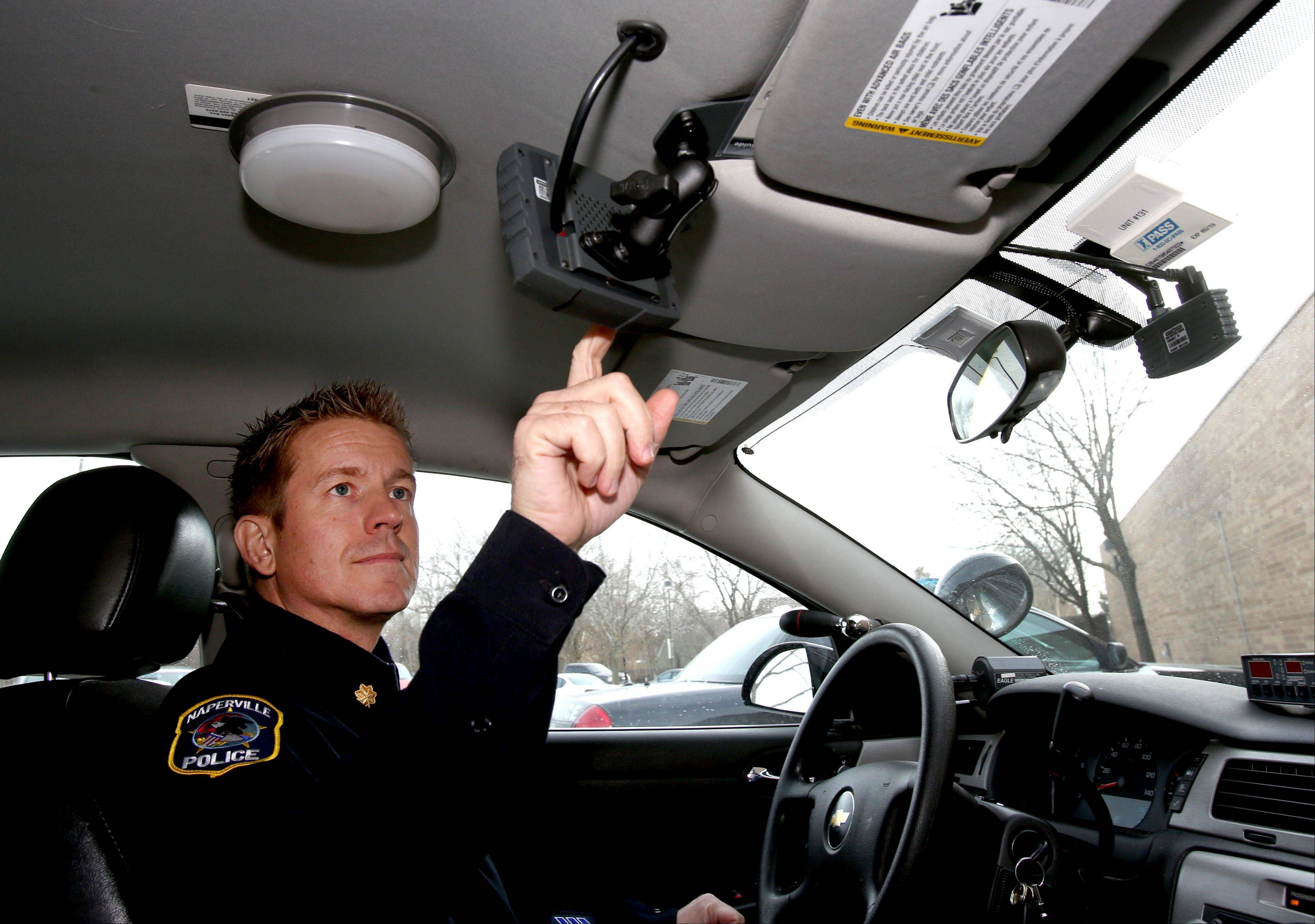 Naperville Cmdr. Jason Arres adjusts a monitor for a new camera, seen on the right, being installed in city police cars.