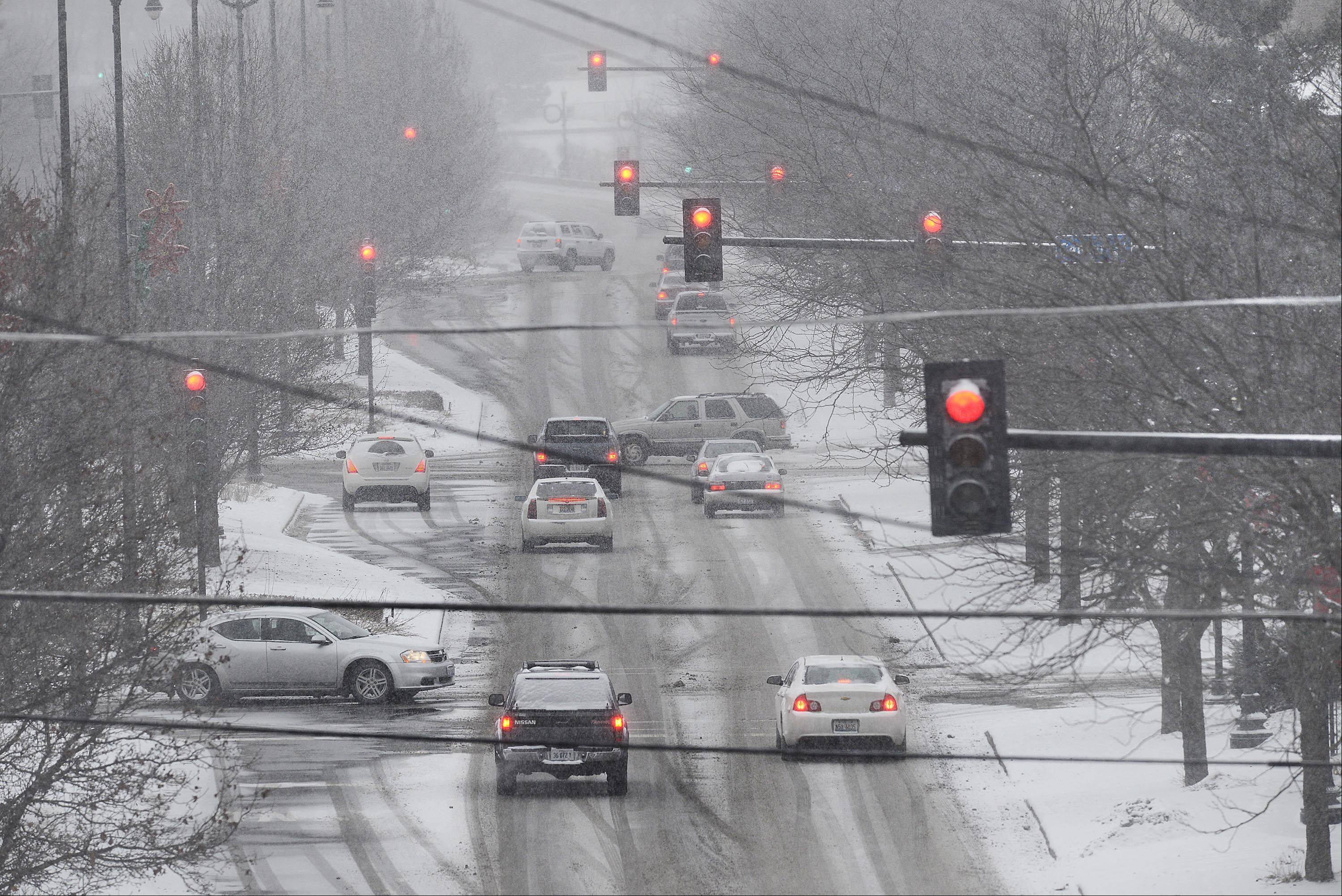 Traffic moves slowly on Kimball Street in Elgin as the incoming snowstorm begins Tuesday afternoon.