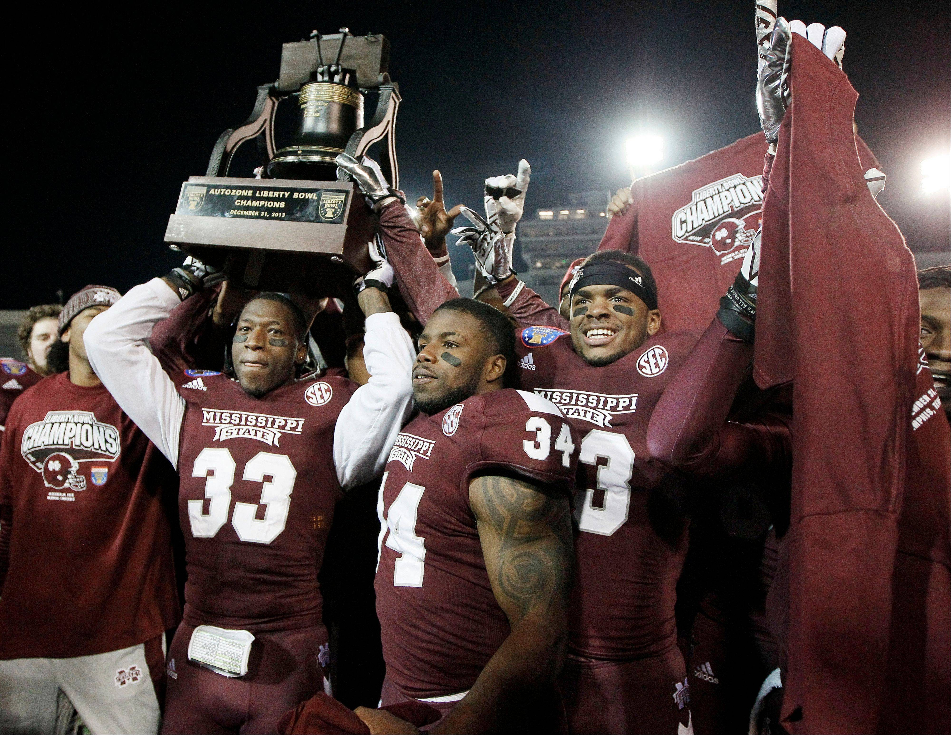 Mississippi State players Kivon Coman, from left, Josh Robinson and Michael Hodges celebrate with the trophy after beating Rice in the Liberty Bowl on Tuesday in Memphis, Tenn.