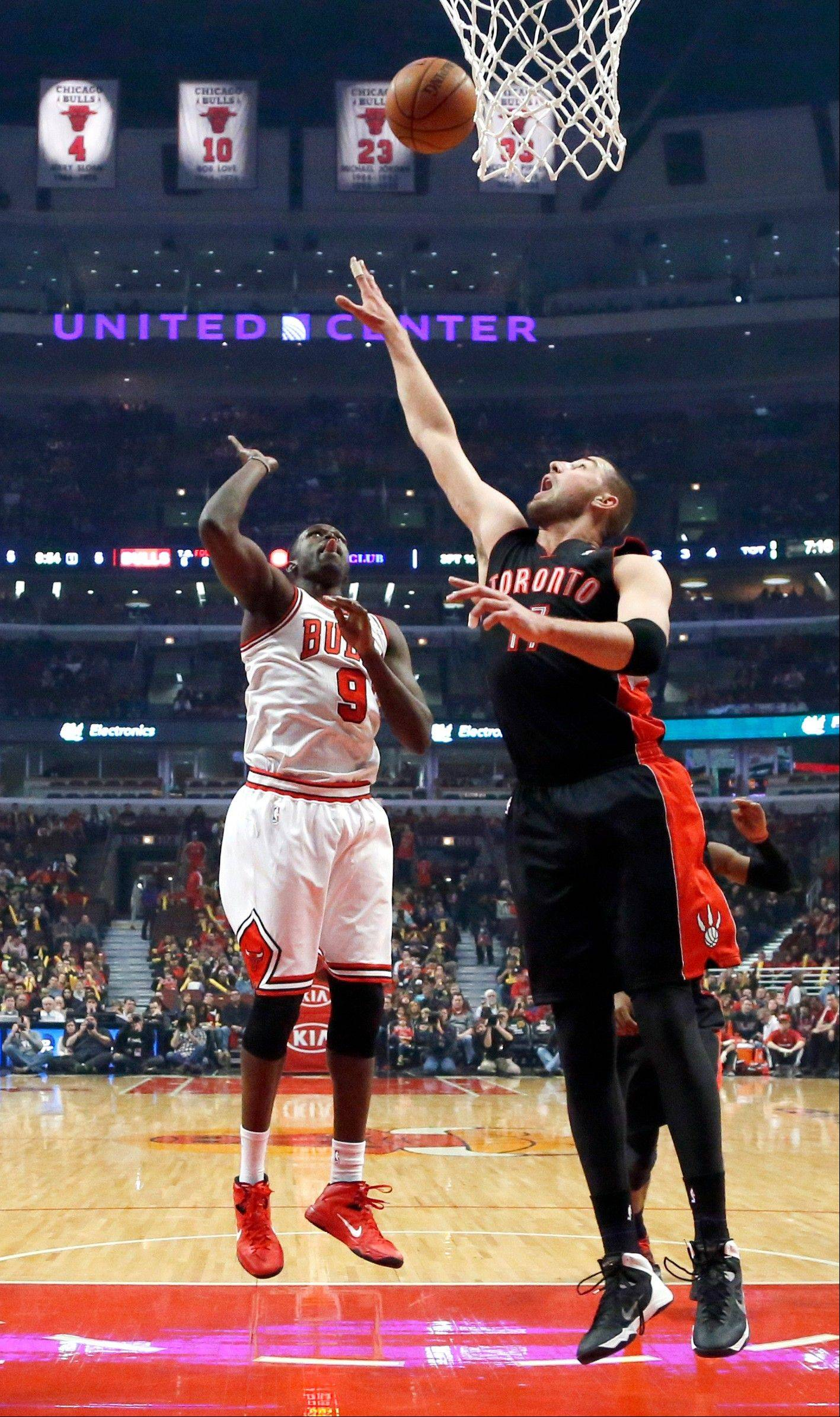 Chicago Bulls forward Luol Deng (9) watches his shot score over Toronto Raptors center Jonas Valanciunas during the first half of an NBA basketball game Tuesday, Dec. 31, 2013, in Chicago. (AP Photo/Charles Rex Arbogast)