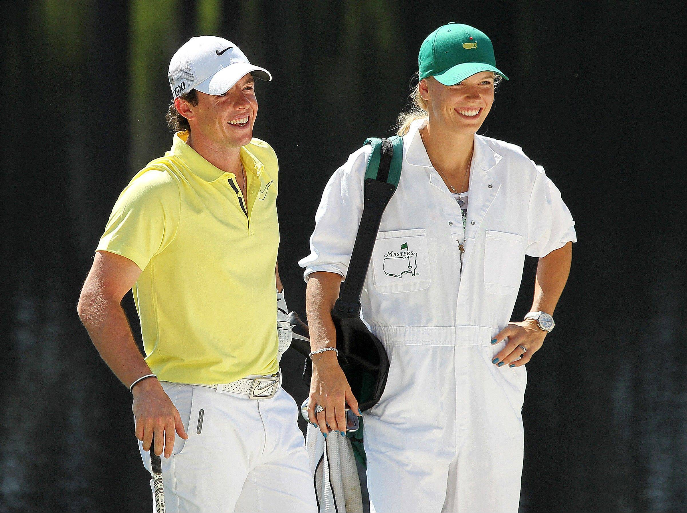Rory McIlroy and his caddie, tennis player Caroline Wozniacki, share a laugh on the fourth hole during the par-3 competition at the Masters golf tournament in April. The couple announced their engagement on Twitter Tuesday.