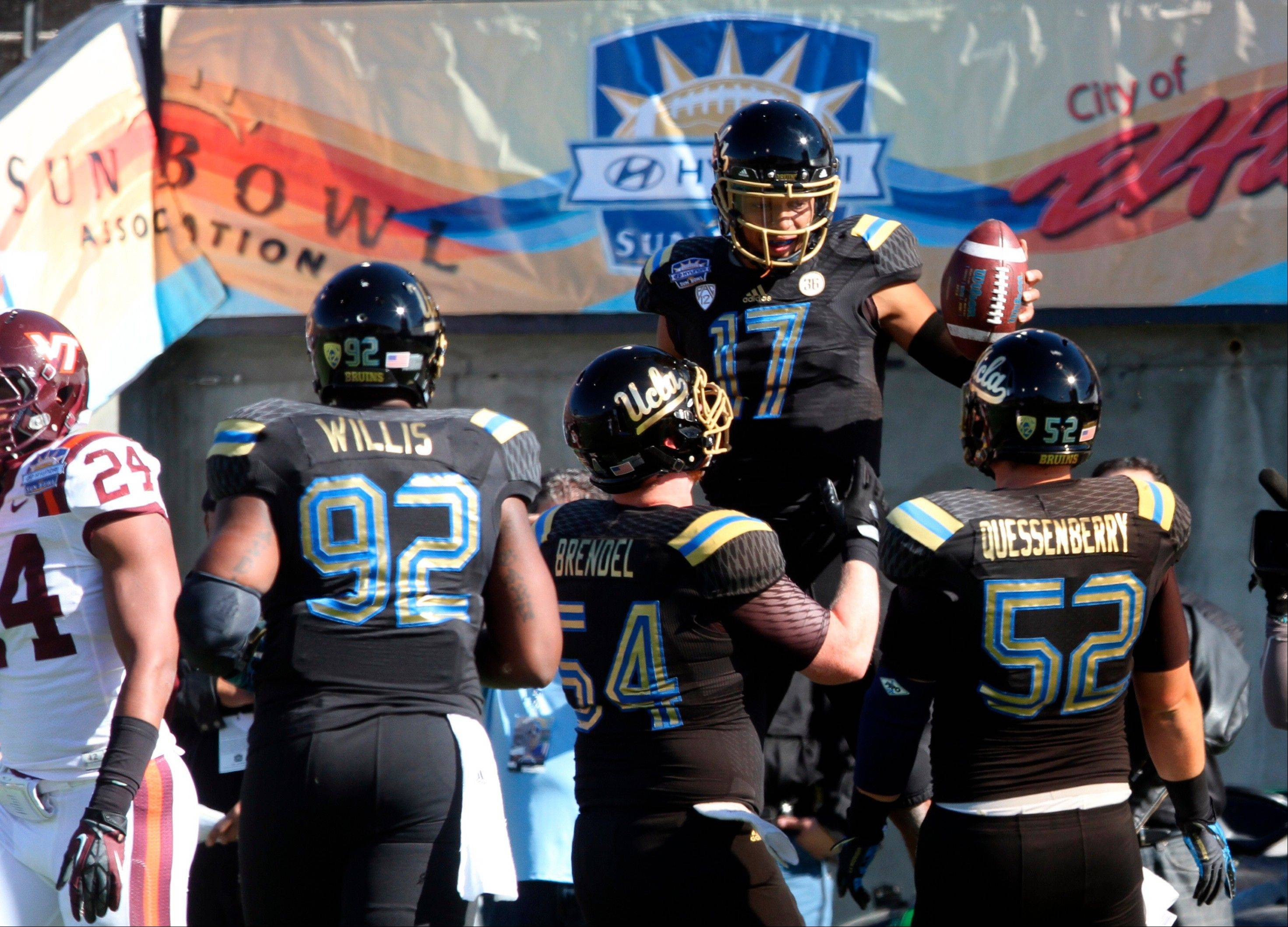 UCLA quarterback Brett Hundley (17) celebrates with teammates after a first-quarter touchdown against Virginia Tech in the Sun Bowl on Tuesday in El Paso, Texas.