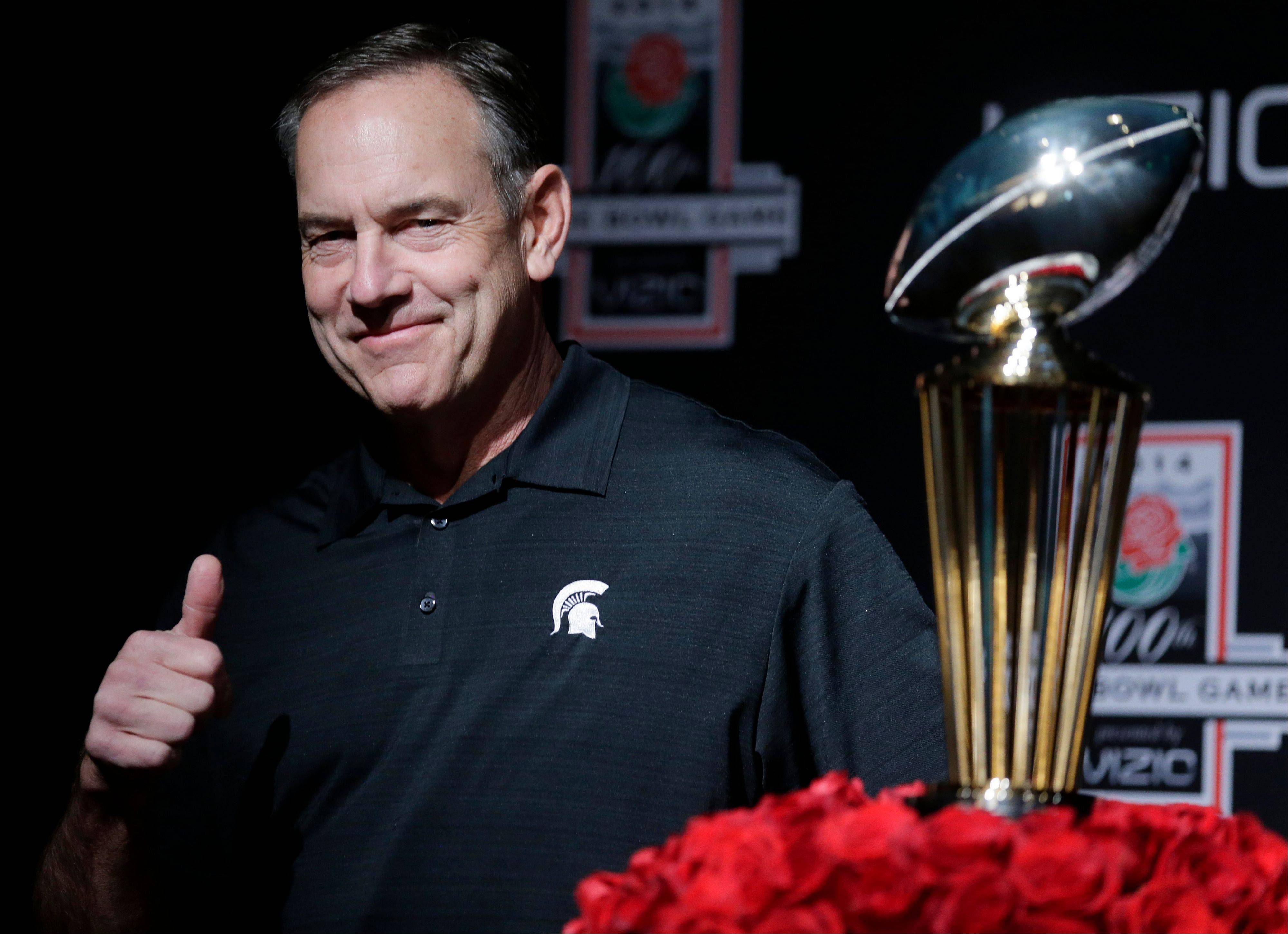 Michigan State head coach Mark Dantonio poses by the Rose Bowl trophy after a news conference Monday in Los Angeles. The Spartans will play in Pasadena Wednesday for the first time since 1988.