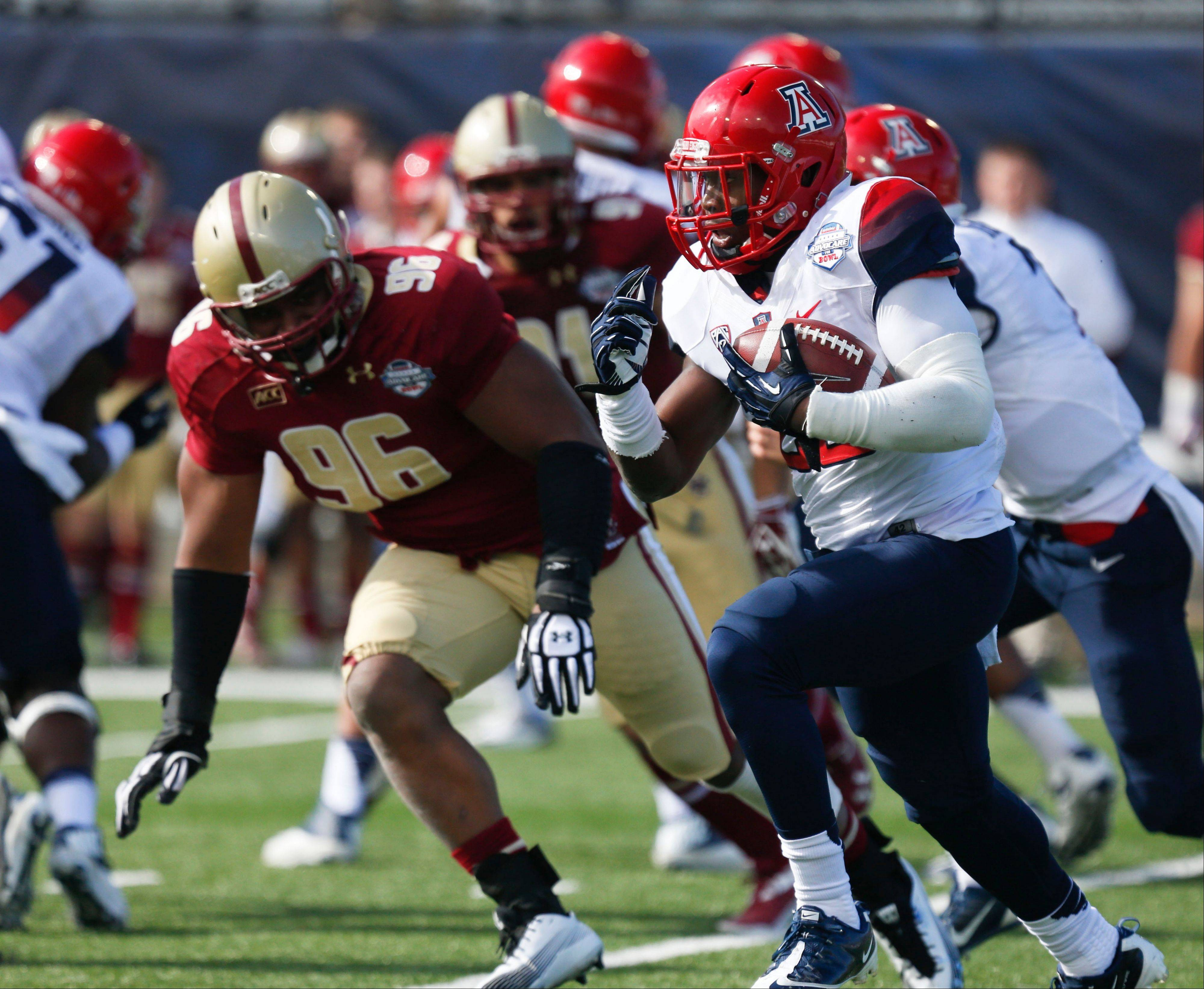 Arizona running back Ka'Deem Carey rushes upfield as Boston College defensive lineman Kaleb Ramsey pursues during the first half of the AdvoCare V100 Bowl on Tuesday at Independence Stadium in Shreveport, La.