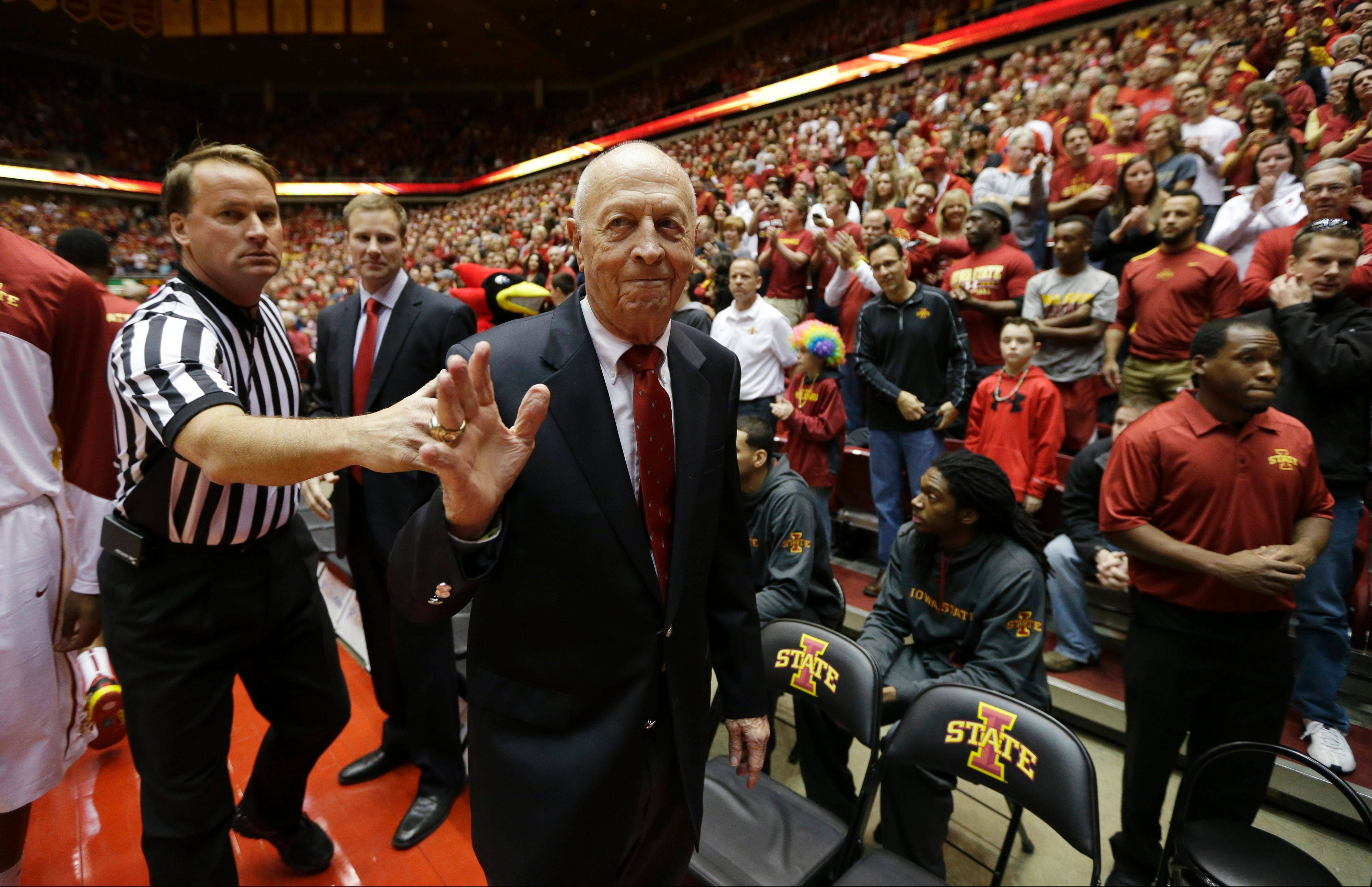 Former Iowa State basketball coach Johnny Orr waves to fans as he walks off the court before a basketball game between Iowa State and Michigan on Nov. 17, 2013, in Ames, Iowa. Orr coached at Michigan for 12 seasons before directing the Cyclones from 1980-94.