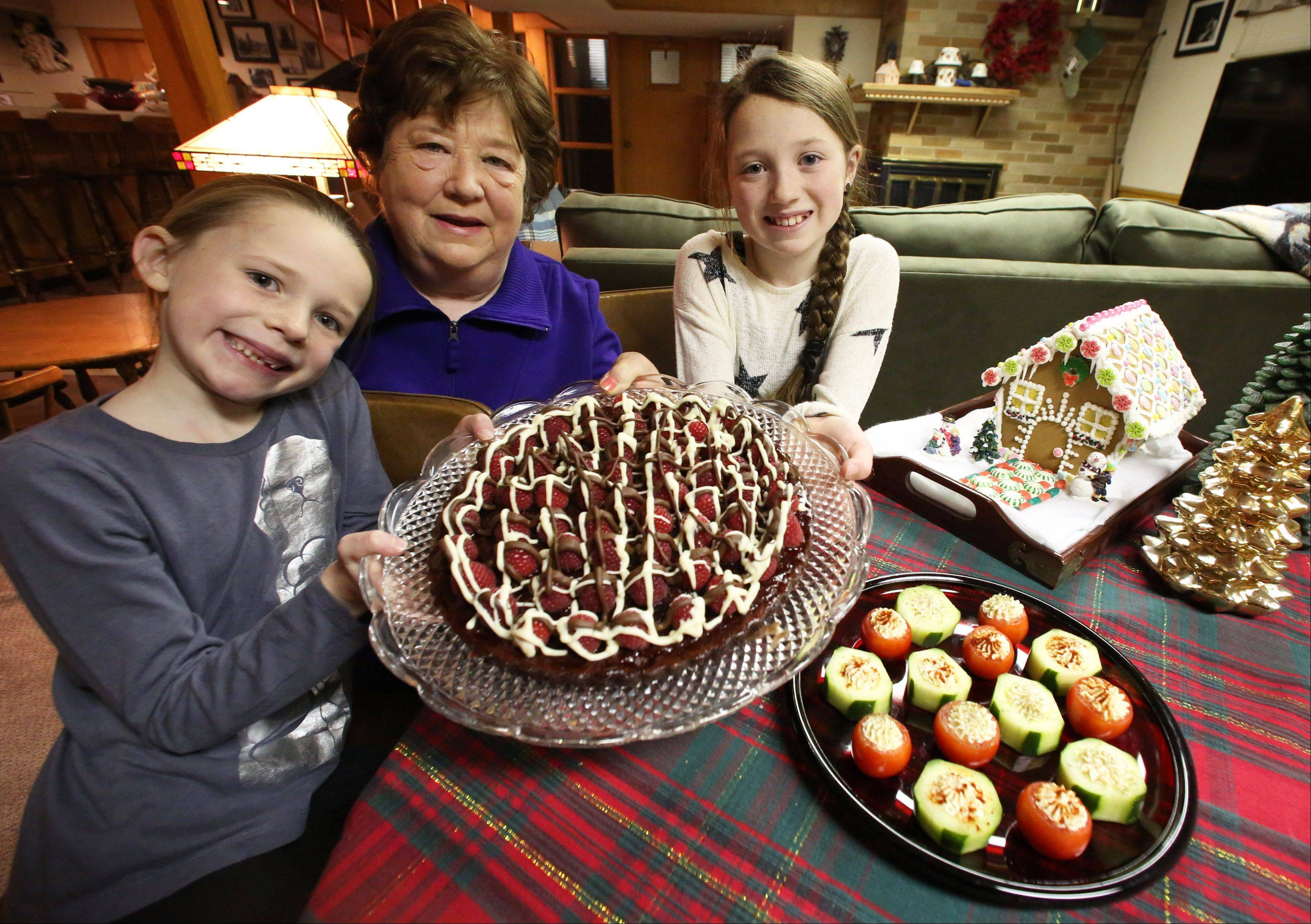 Anola Stowick and her granddaughters Allie Edwards, 7, and Madison Edwards, 10, holding chocolate raspberry torte and on the side stuffed cucumbers and campari tomatoes.