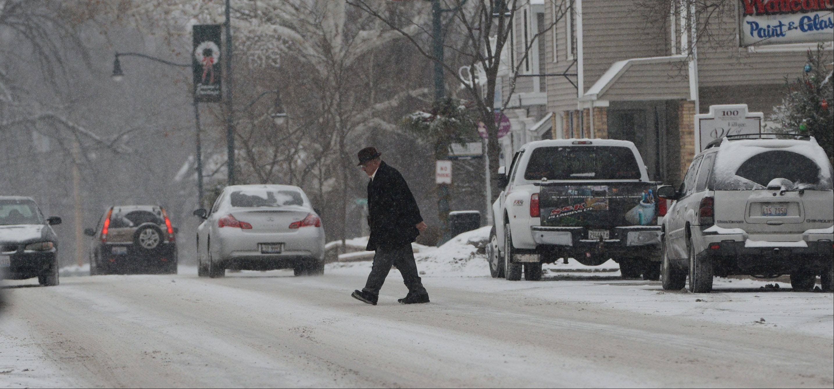 Pedestrians make their way across a snow-covered Main Street in downtown Wauconda Tuesday as a winter storm moves into the area.