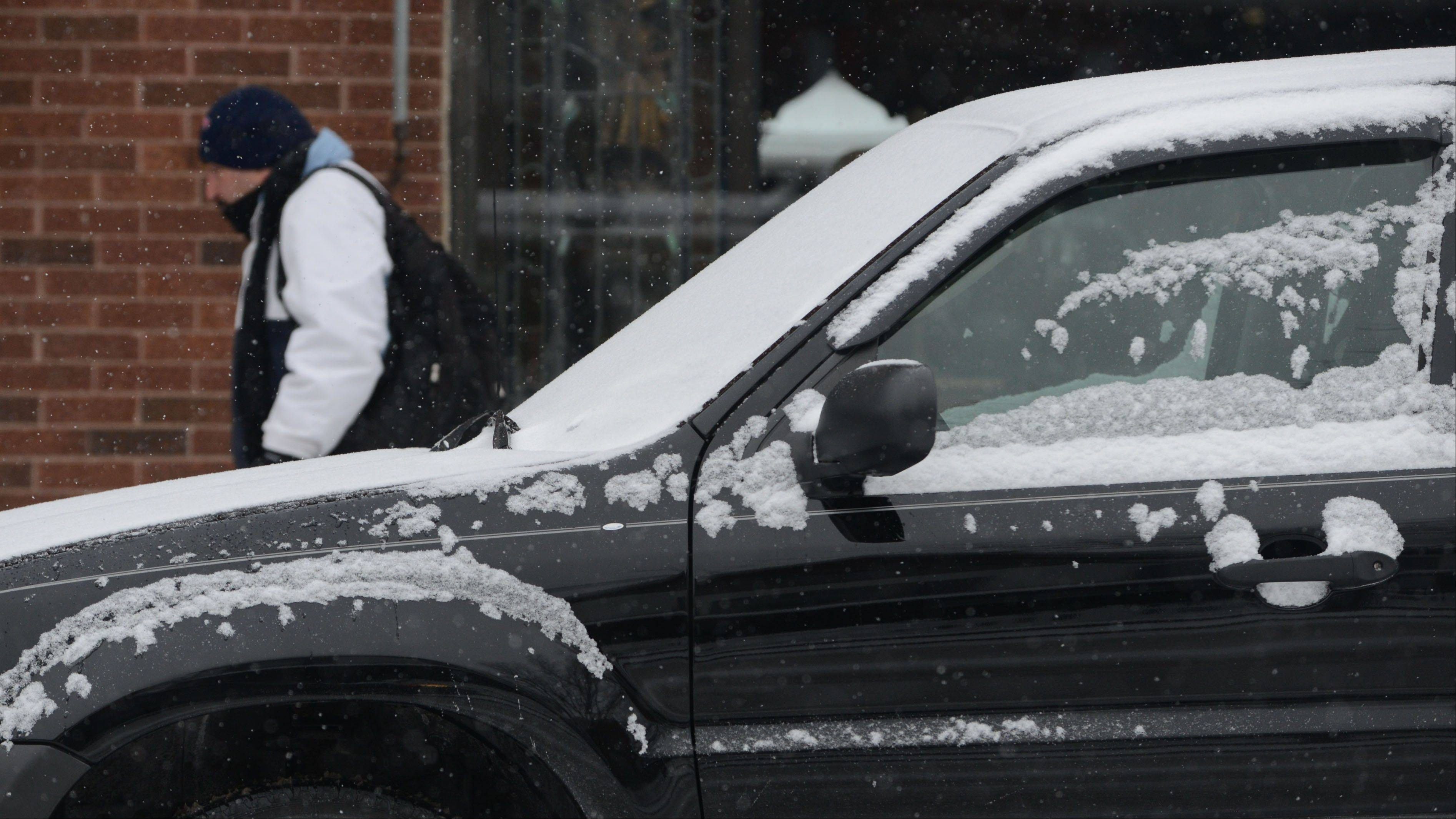 Snow begins to collect on cars parked along Main Street in downtown Wauconda New Year's Eve as a winter storm moves into the Chicago area.