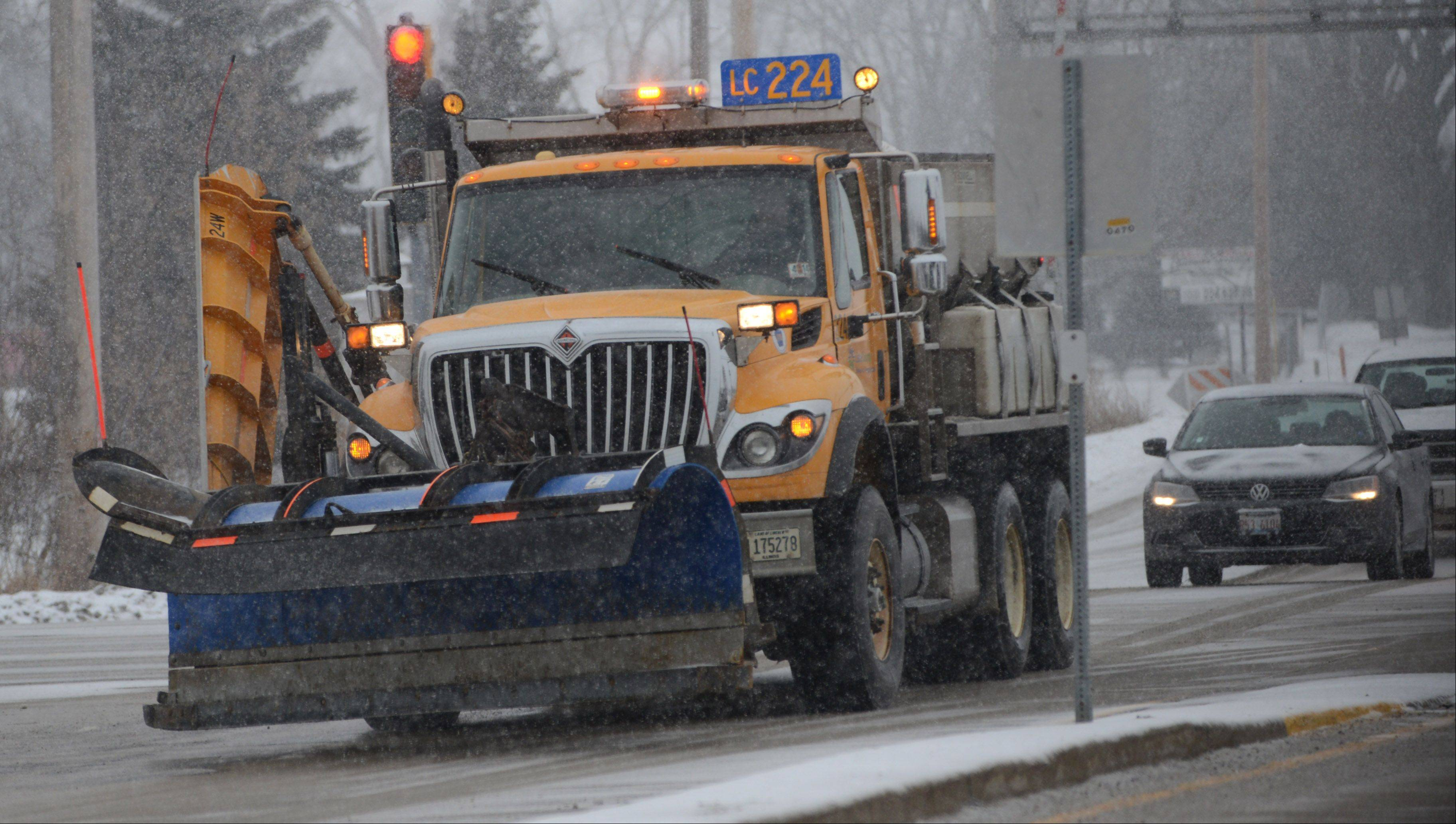 Lake County Department of Transportation plows head down Winchester Road in Libertyville Tuesday afternoon as a winter storm moves in to the Chicago area.
