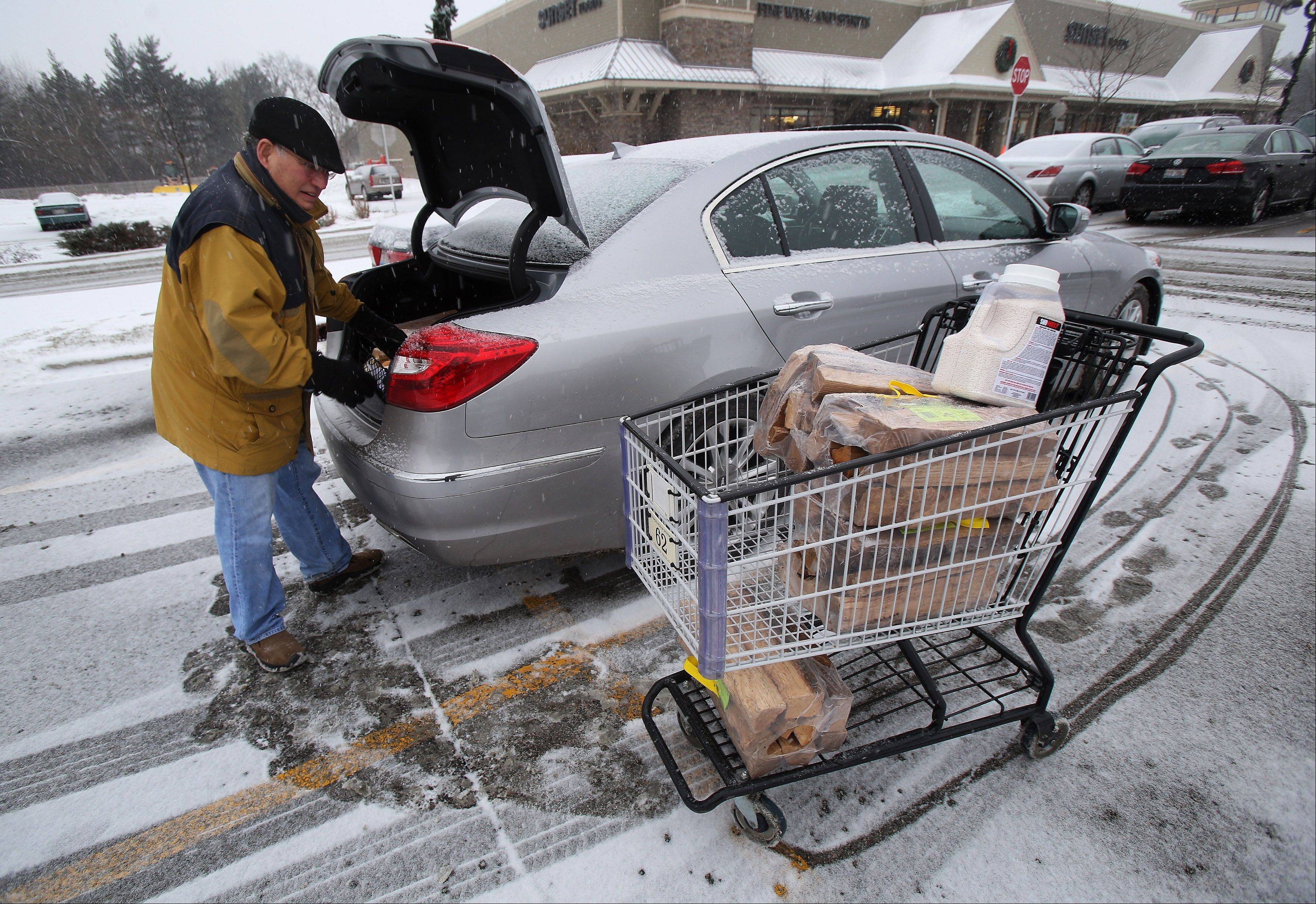 Long Grove resident Dom Rizzi loads his car with firewood and salt at Sunset Foods in Long Grove in preparation for the snow that started falling Tuesday.