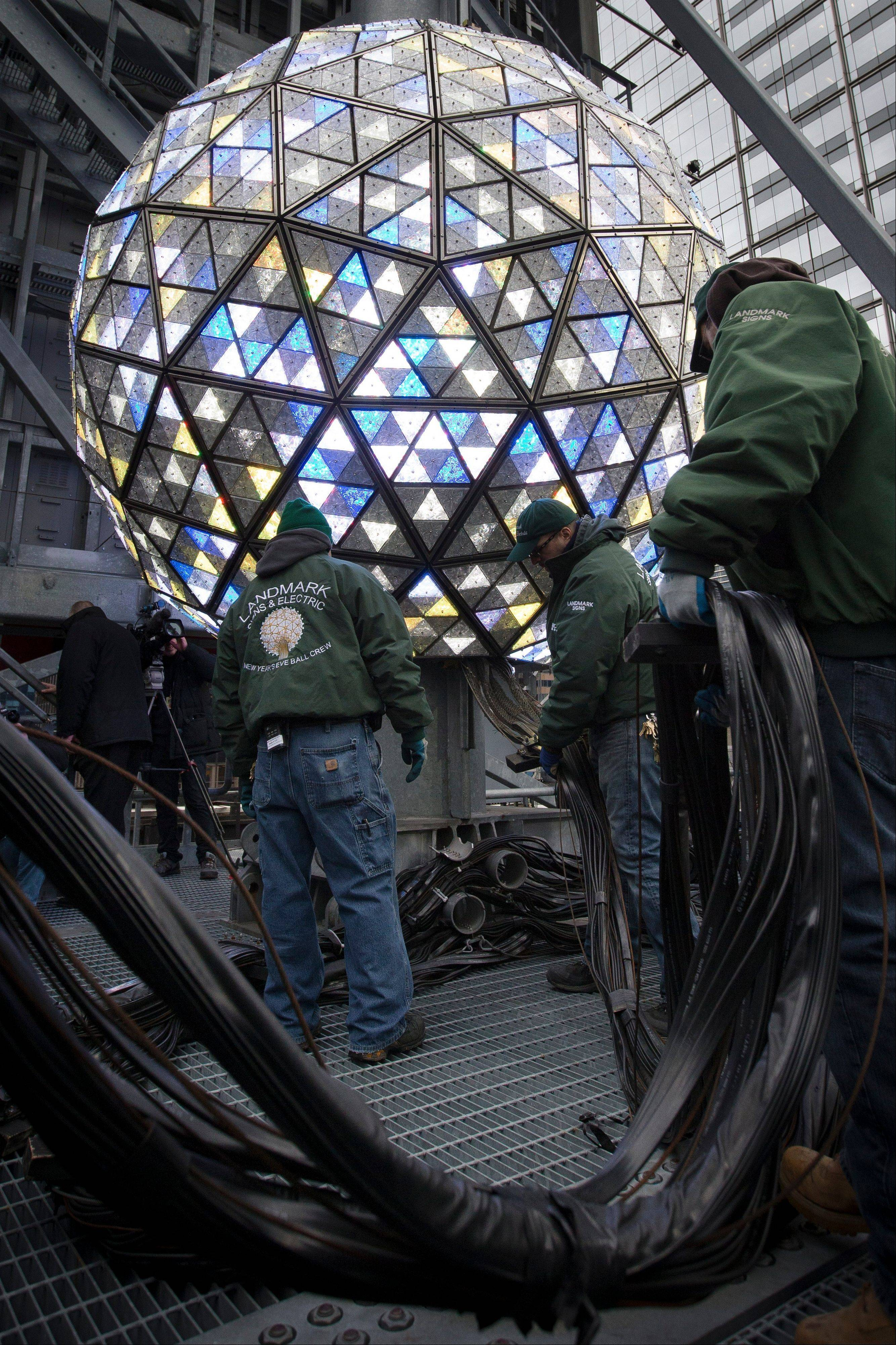 Workers handle cables attached to the New Year's Eve ball during a test atop the 1 Times Square building Monday in New York. The iconic 11,875-pound geodesic sphere covered in 2,688 Waterford Crystal triangles will descend a 130-foot pole to mark the stroke of midnight during the annual Times Square celebration.