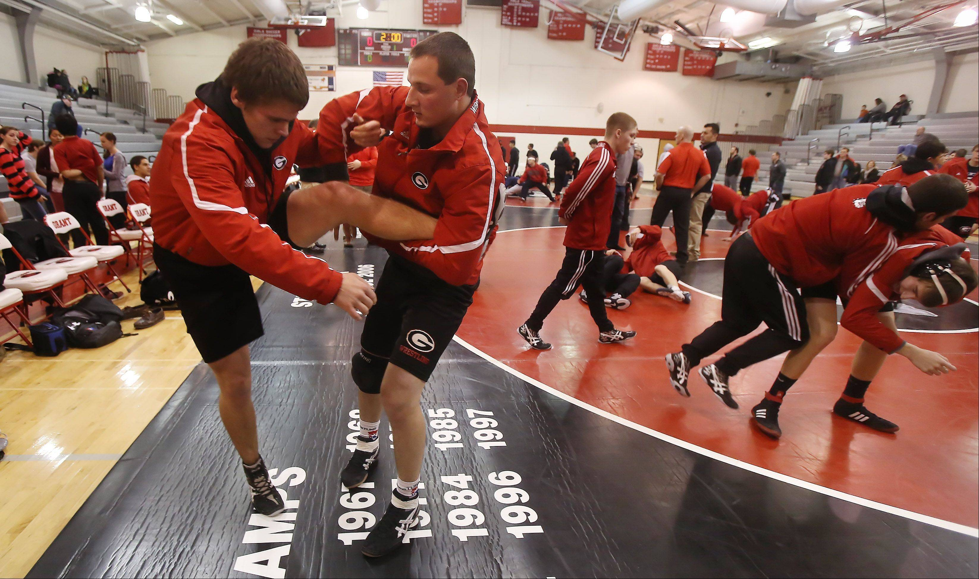 Grant Community High School wrestlers Steve Herrington, left, and Anthony Mostachio warm up before a recent home meet. The annual school report card now lists sports and other activities to paint a more complete picture for parents, state education officials say.