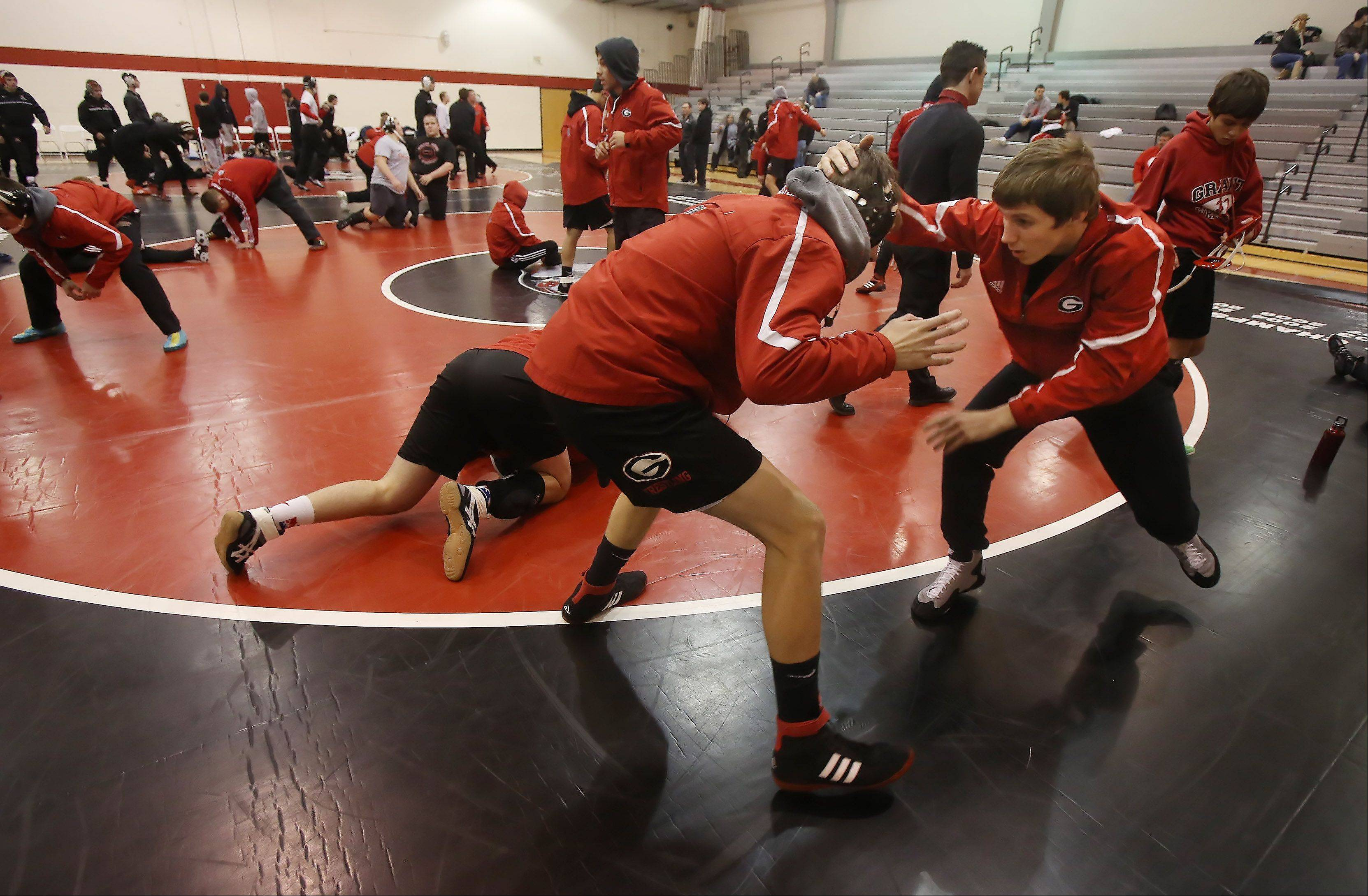 Grant Community High School wrestlers warm up before a recent home meet. Educators find value in the state now listing extracurricular activities on schools' annual report cards.