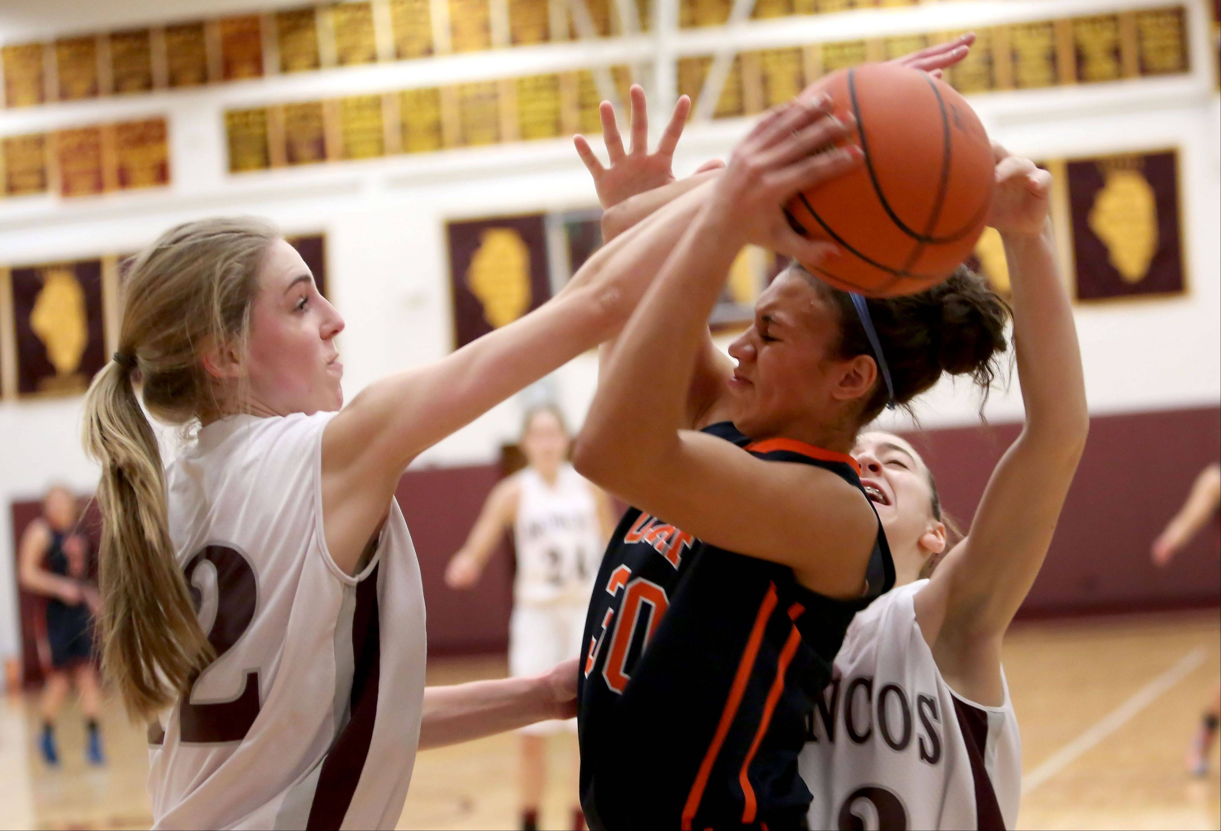 Kelly Karlis, left, and Claudia Kunzer, right, of Montini put the pressure on Oak Park River Forest's Chardonnay Harris Monday at the Montini Christmas tournament in Lombard.