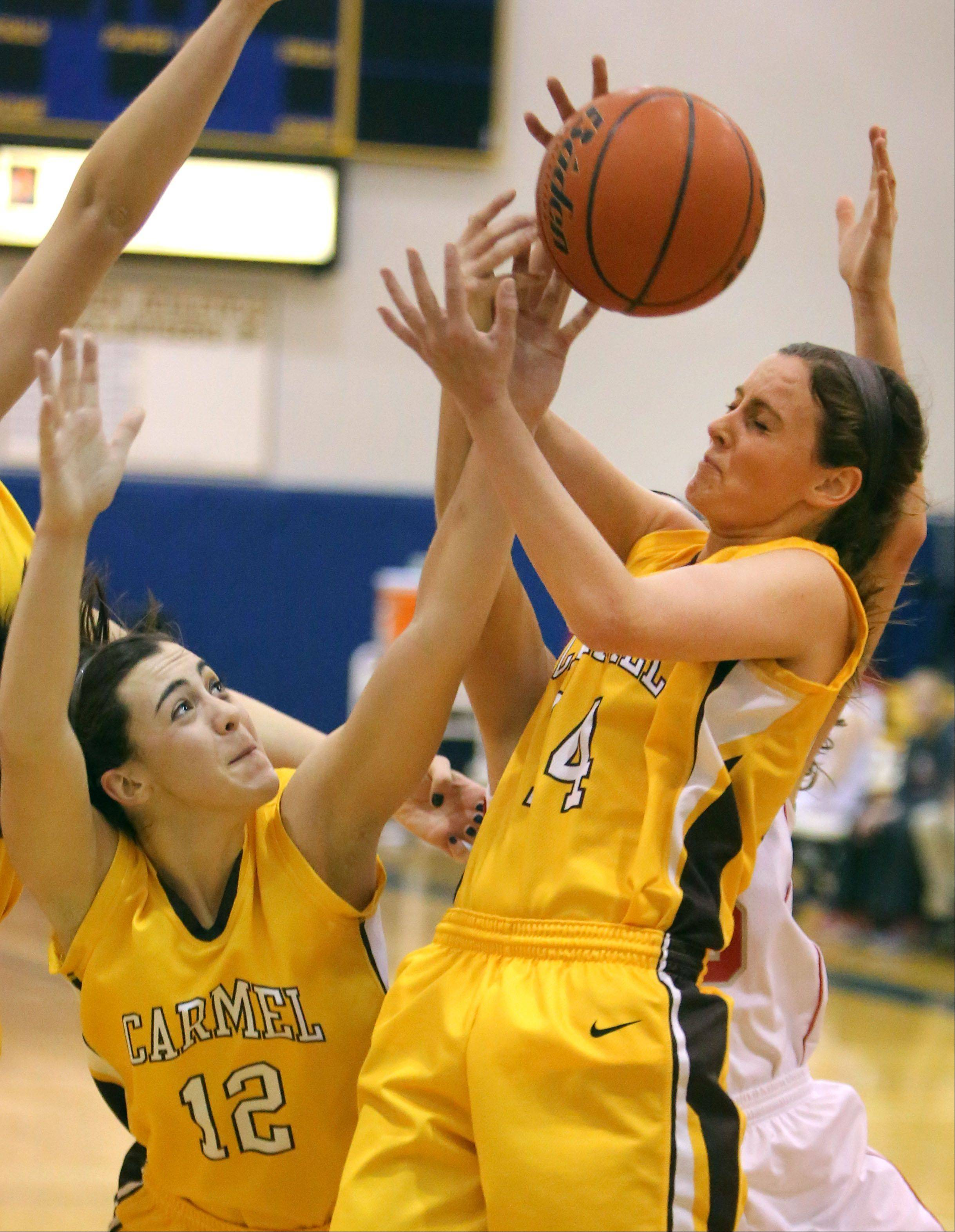 Carmel's Kathleen Felicelli, left, and Casidy Kloss battle for a rebound during Friday's game at Warren.