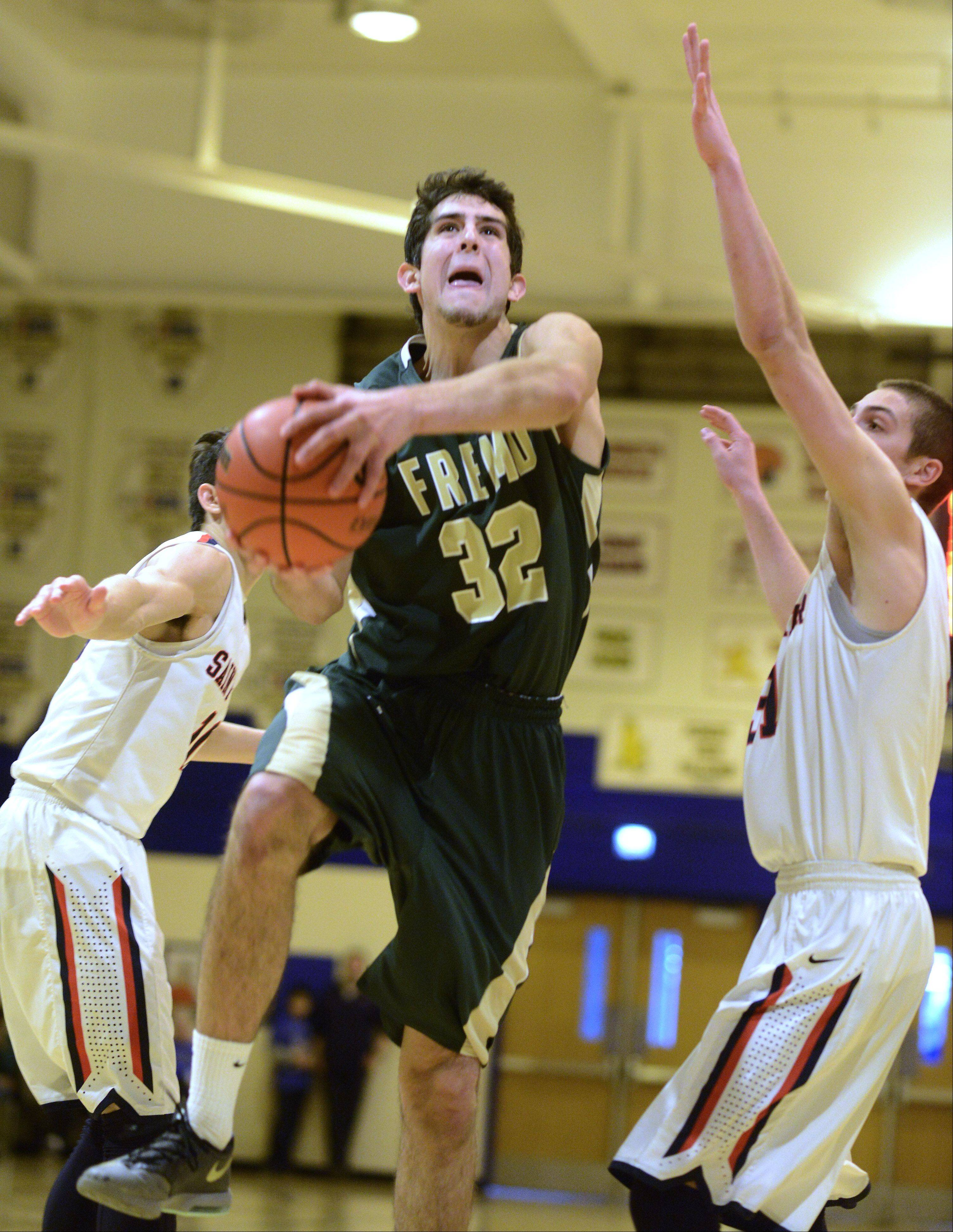 Fremd's Matt Ochoa steps between St. Viator's Robert Grant, left, and Sal Cannella for a layup Saturday.