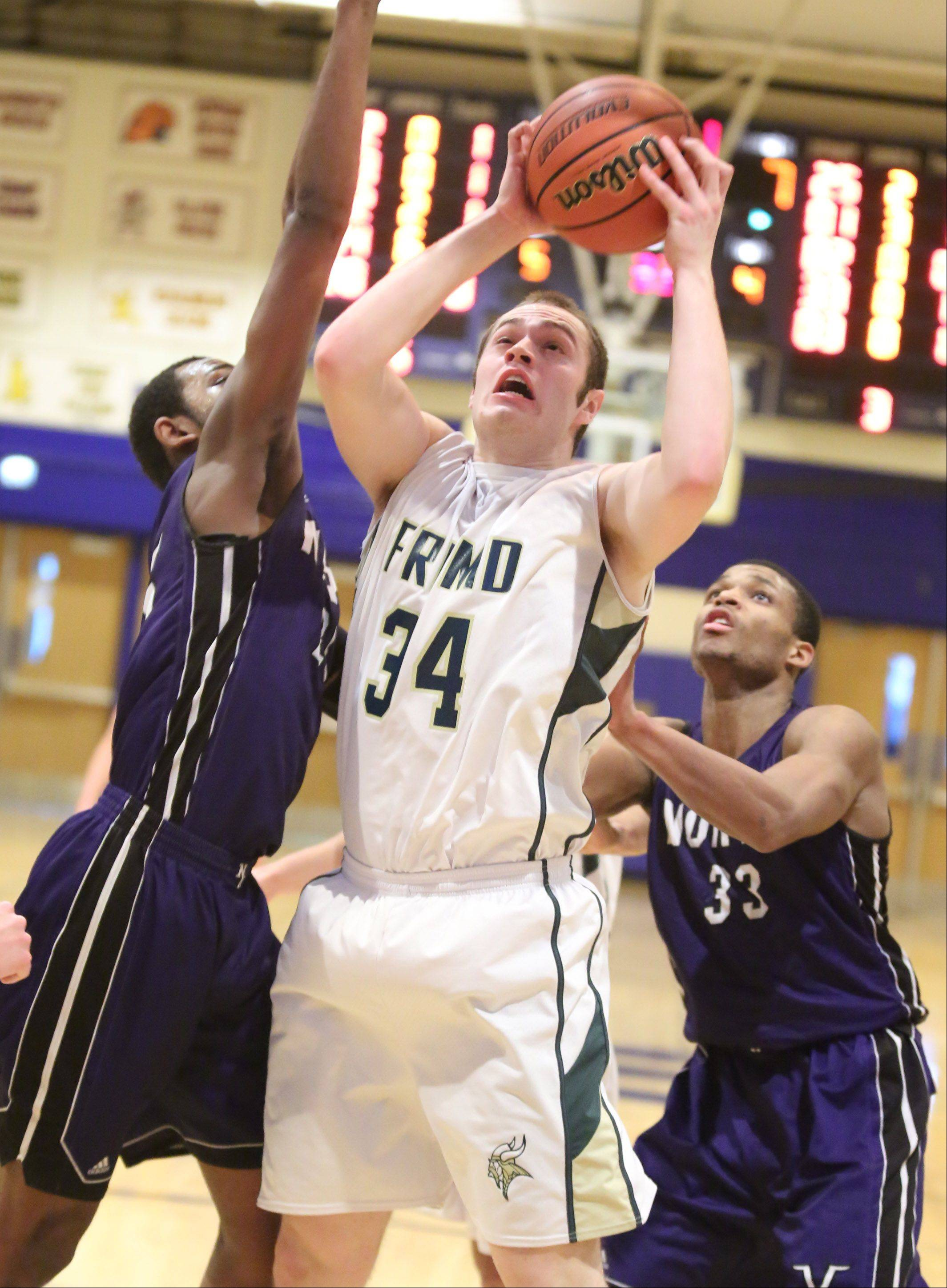 Fremd's Benjamin Carlson take s shot between Niles North defenders including Duante Stephens, right, on Thursday at the Wheeling Hardwood Classic.