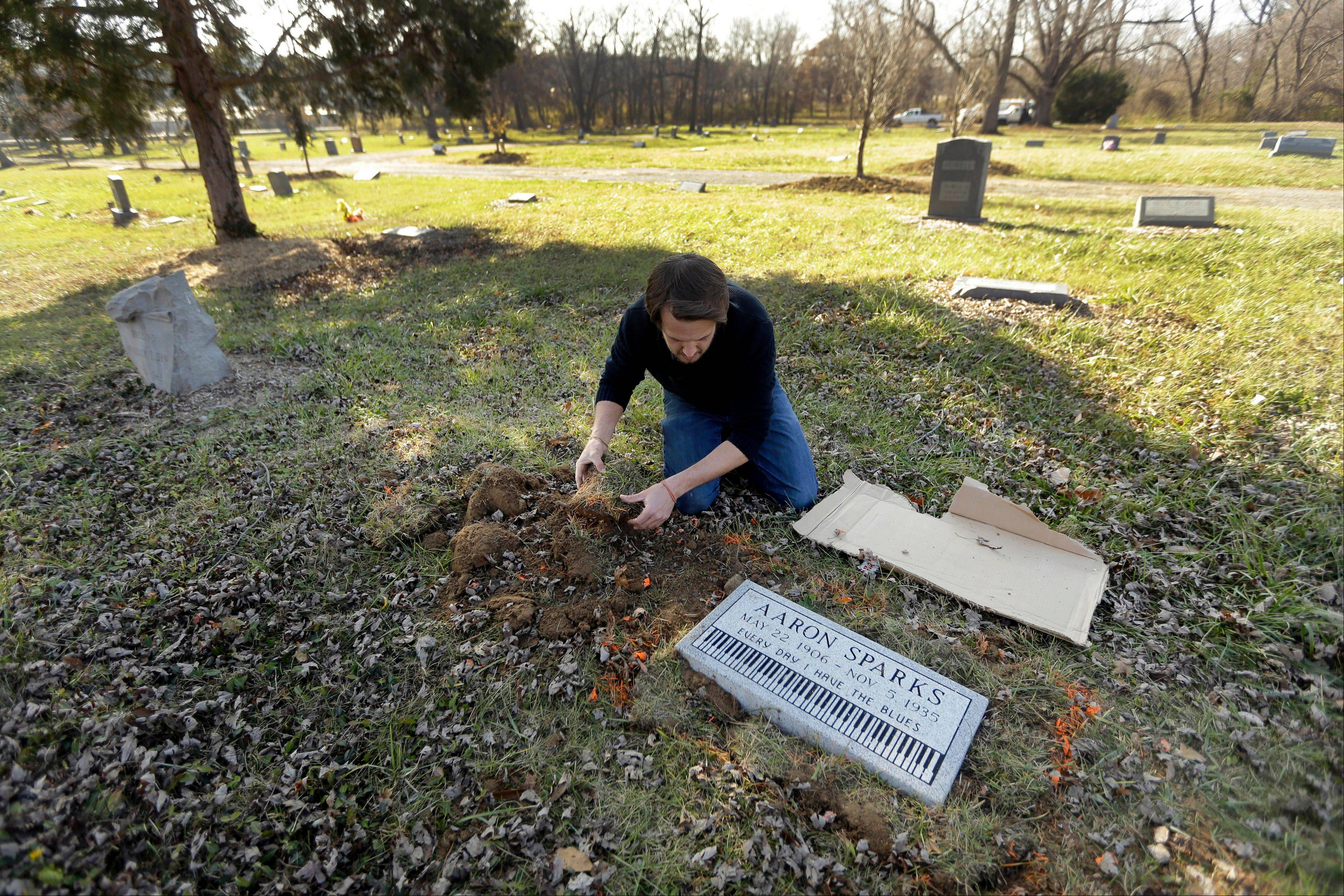 Aaron Pritchard replaces grass after laying a headstone on the previously unmarked grave of blues musician Aaron Sparks in Crestwood, Mo. Pritchard is part of the Killer Blues Headstone Project, a nonprofit effort to posthumously honor sometimes long-forgotten blues musicians with grave markers.