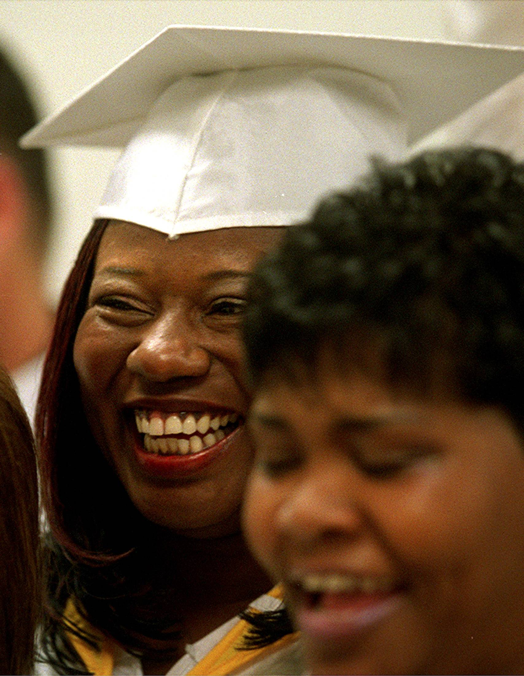 Vernita McGee (left) of Aurora and Kimberlee Morris (right) of Elgin share a laugh with fellow graduates as they prepare to march during the Kane County Drug Court graduation at Christ Community Church in St Charles on Thursday.