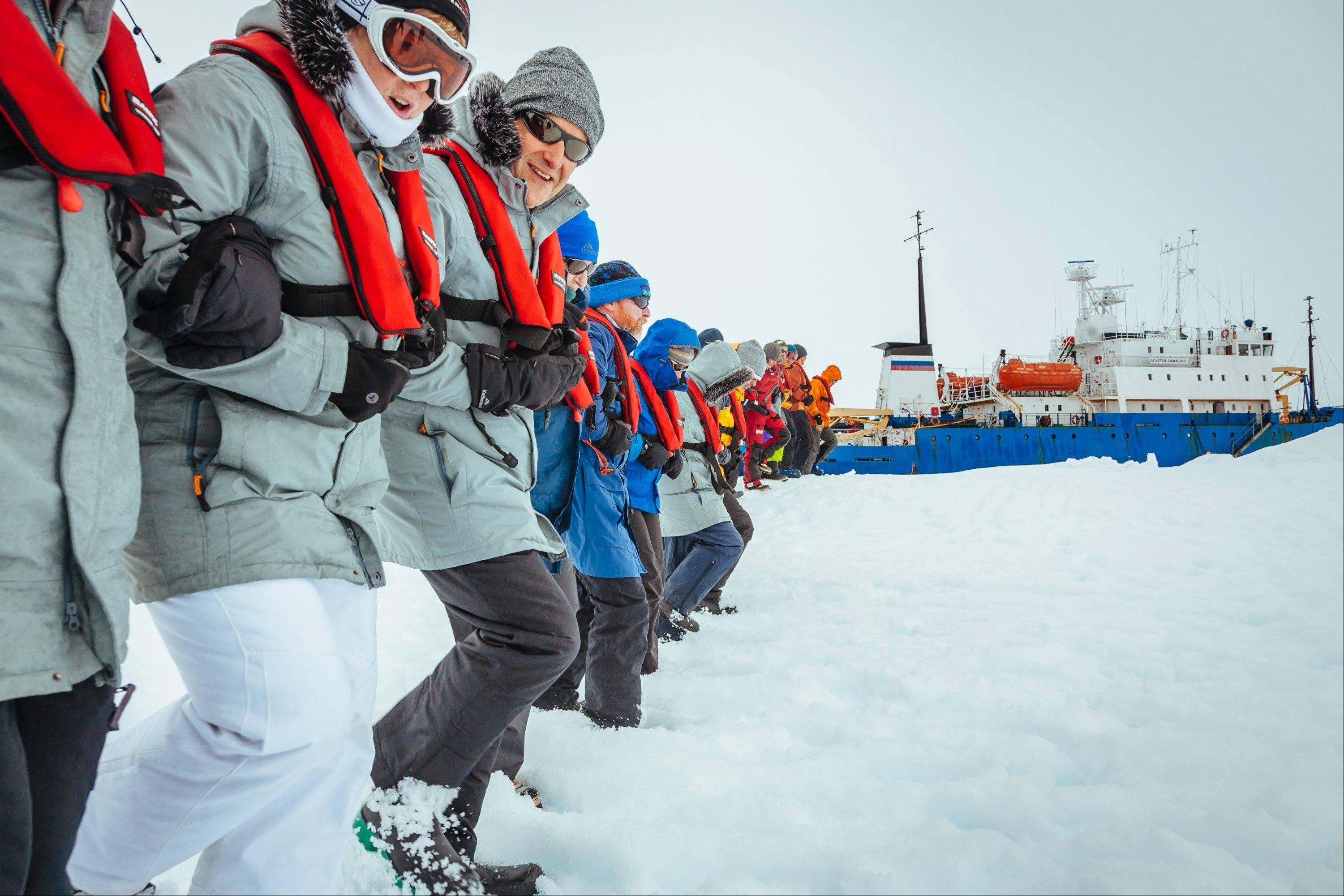 Passengers link arms and stamp out a helicopter landing site on the ice near the trapped ship in Antarctica on Tuesday.