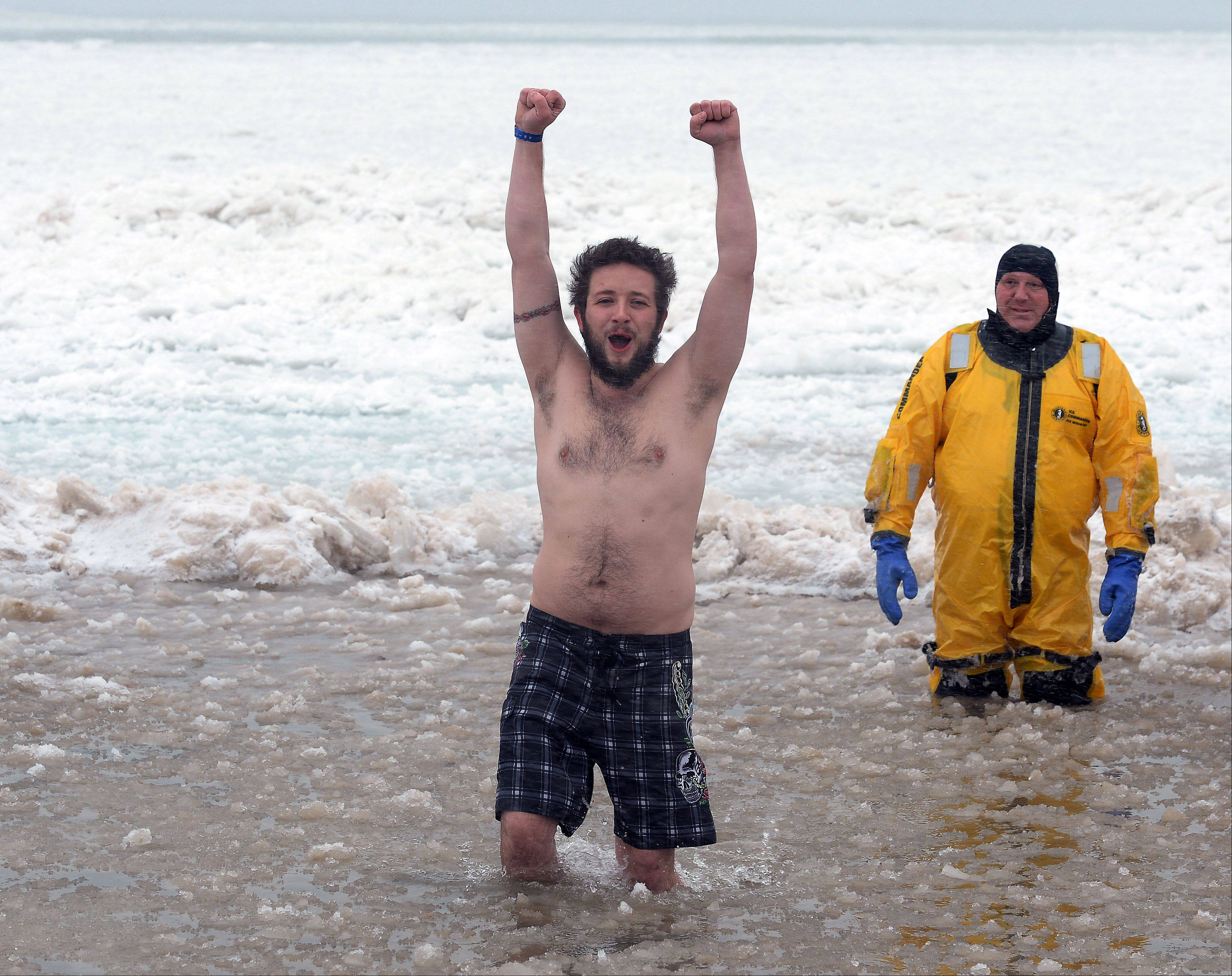 Brad Paschall of Waukegan feels victorious as he braves the freezing Lake Michigan water celebrating the new year during the 15th Annual Polar Bear Plunge at Waukegan Municipal Beach.