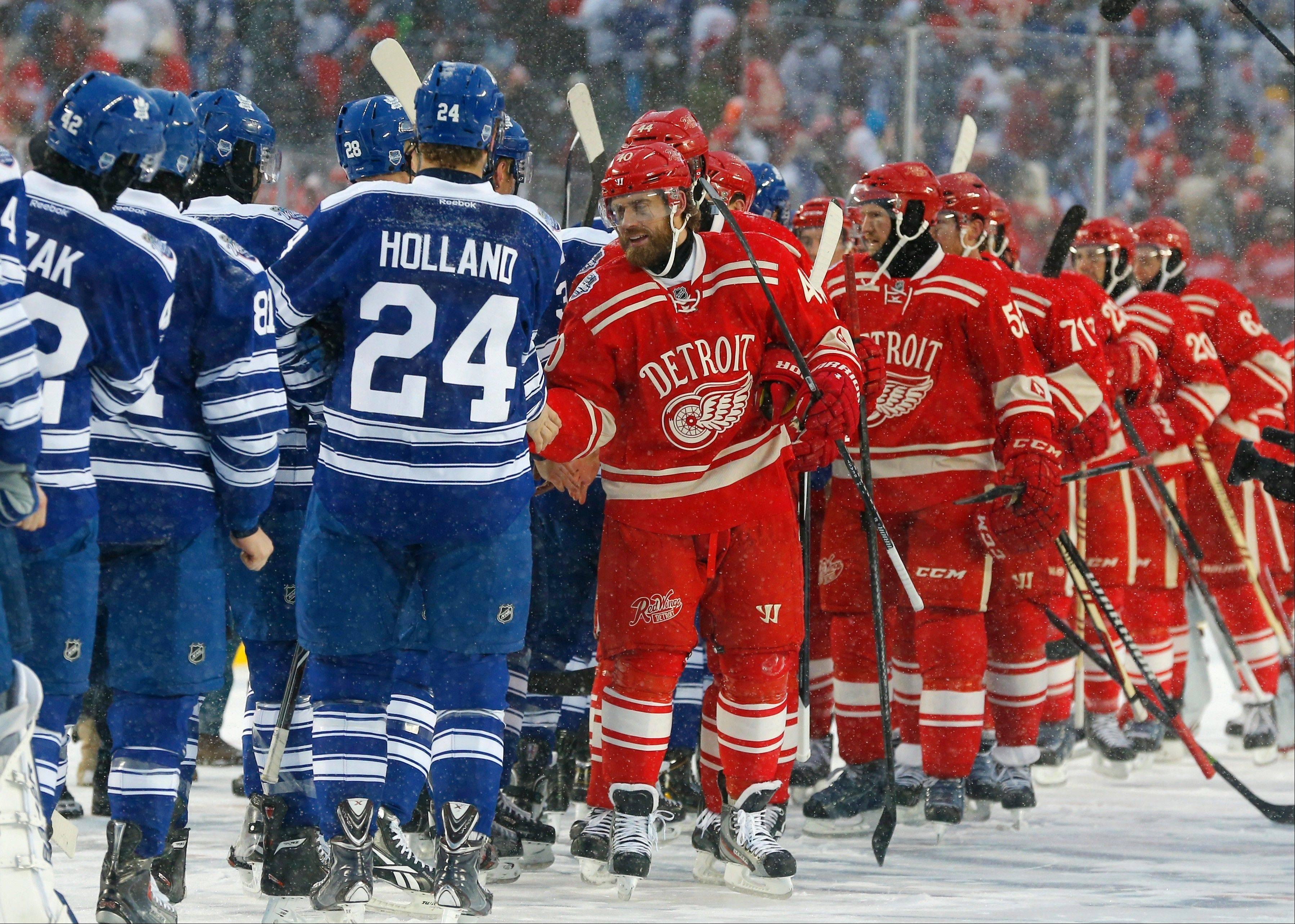 Detroit Red Wings left wing Henrik Zetterberg leads his team as they shake the hands of the Toronto Maple Leafs after the Winter Classic outdoor NHL hockey game at Michigan Stadium in Ann Arbor, Mich., Wednesday, Jan. 1, 2014. The Maple Leafs won 3-2.