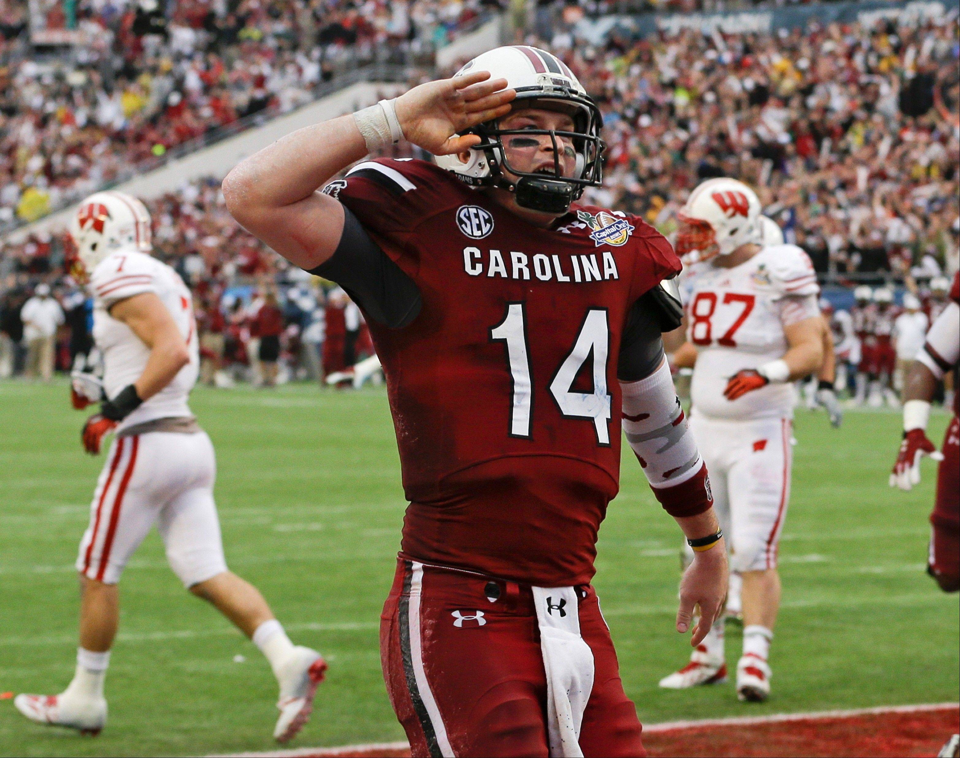South Carolina quarterback Connor Shaw (14) salutes towards fans after catching a touchdown on a pass from receiver Bruce Ellington during the first half of the Capital One Bowl NCAA college football game against Wisconsin in Orlando, Fla., Wednesday, Jan. 1, 2014.