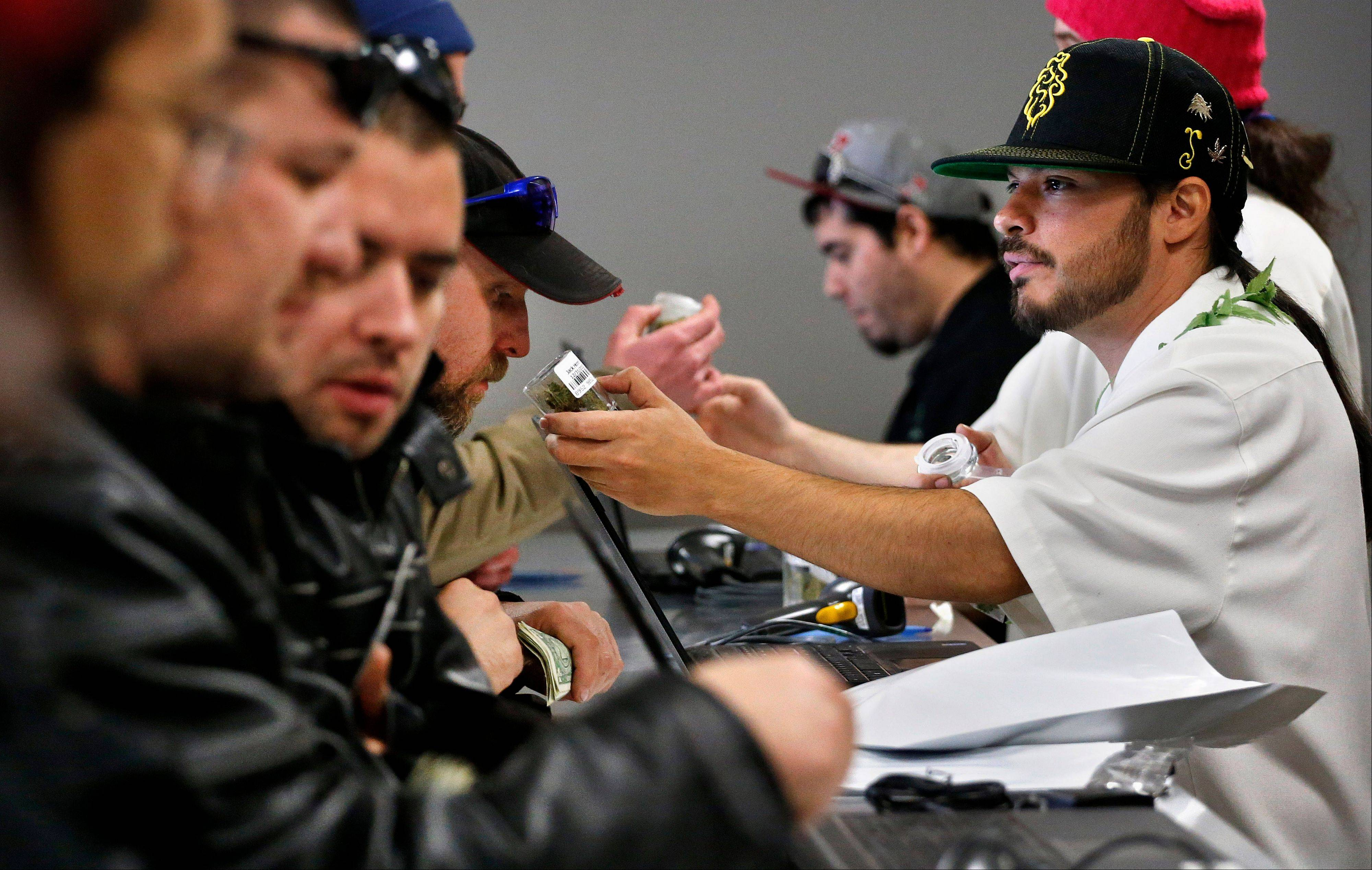 "Employee David Marlow, right, helps a customer, who smells a strain of marijuana before buying it, at the crowded sales counter inside Medicine Man marijuana retail store, which opened as a legal recreational retail outlet in Denver on Wednesday, a day some are calling ""Green Wednesday."""