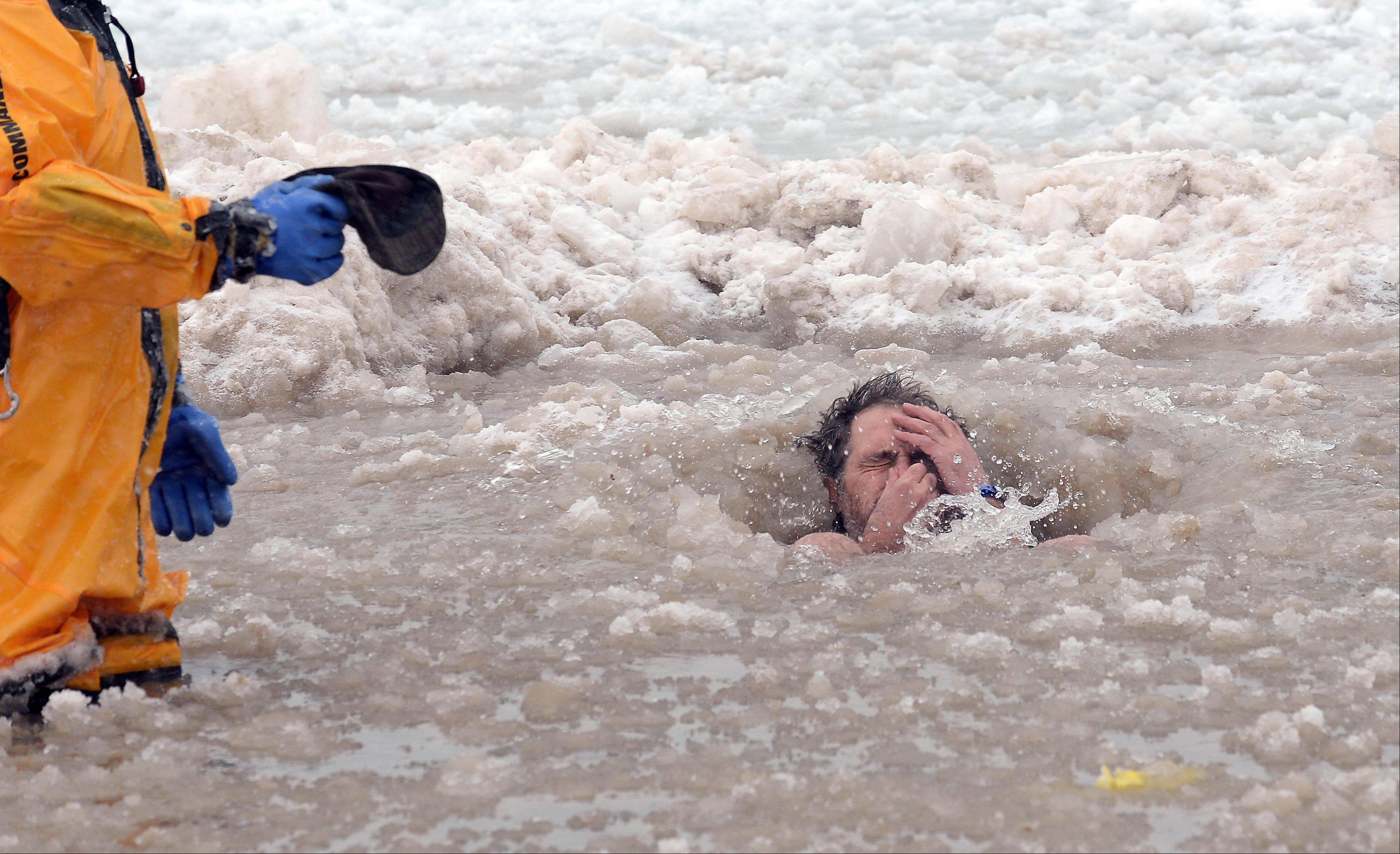 A firefighter holds the hat of Chuck Castellanos of Beach Park as he holds his nose and takes a plunge.