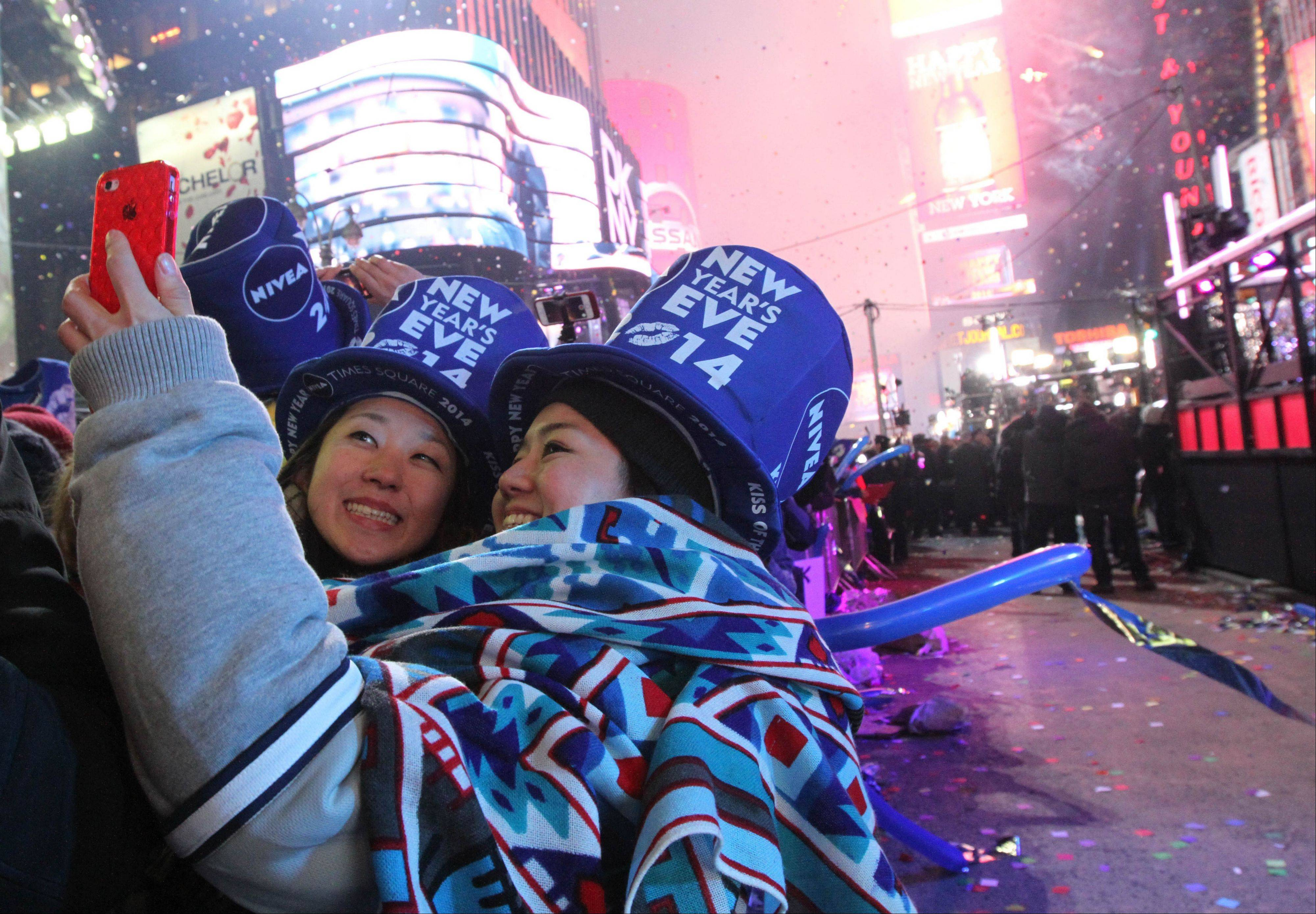 Revelers take part in the festivities in New York's Times Square shortly after midnight New Year's Day Wednesday Jan. 1, 2014.
