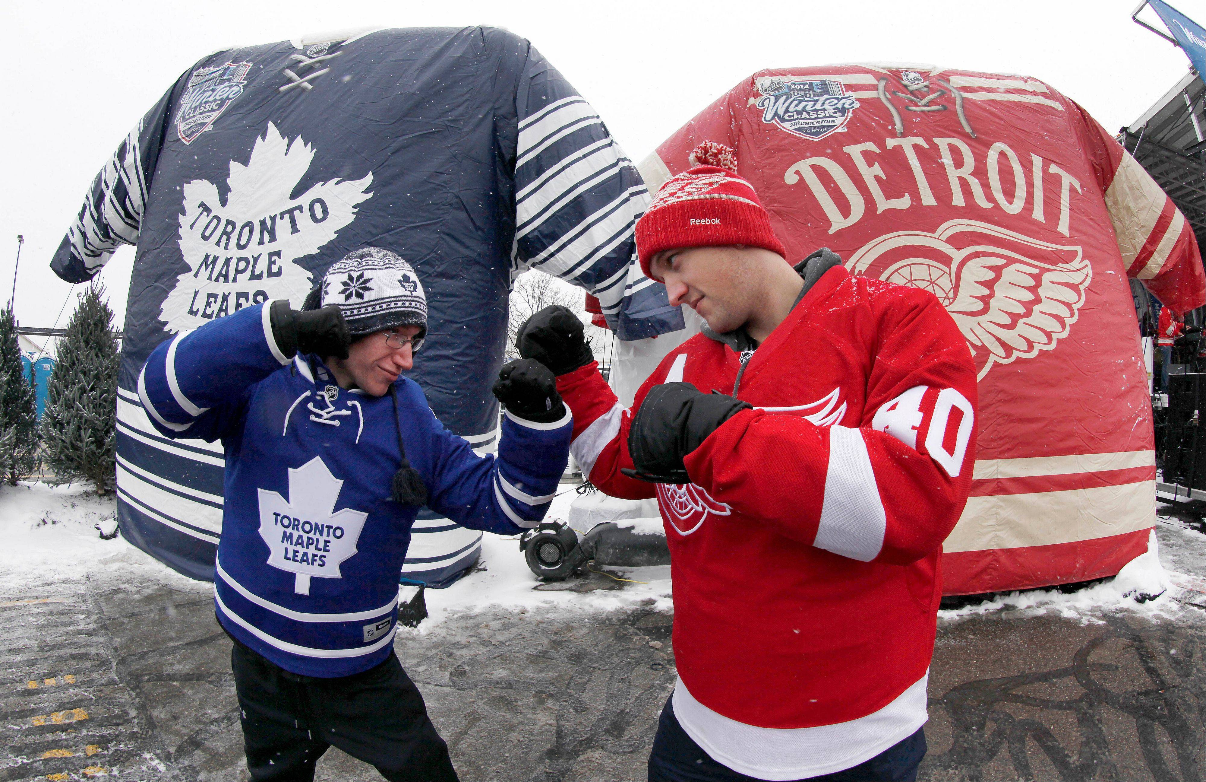Nathan Dunville, of Halifax, Nova Scotia, left, and Adam Boutilier, of Cole Harbour, Nova Scotia, pose for family photographs at the NHL Winter Classic hockey game at Michigan Stadium in Ann Arbor, Mich., Wednesday, Jan, 1. 2014, where the Detroit Red Wings play the Toronto Maple Leafs.
