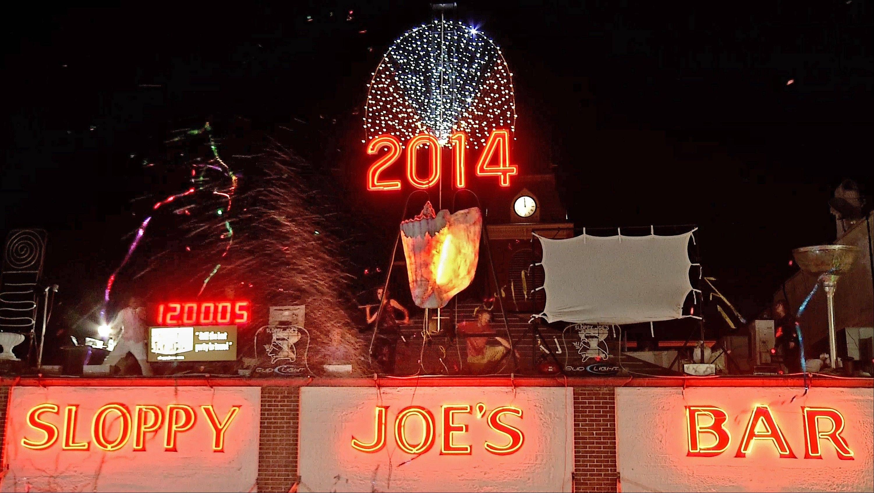 In this photo provided by the Florida Keys News Bureau, a large reproduction of a conch shell is lowered to the roof of Sloppy Joe's Bar in Key West, Fla., early Wednesday, Jan. 1, 2014. The subtropical island city staged four different New Year's Eve drops.