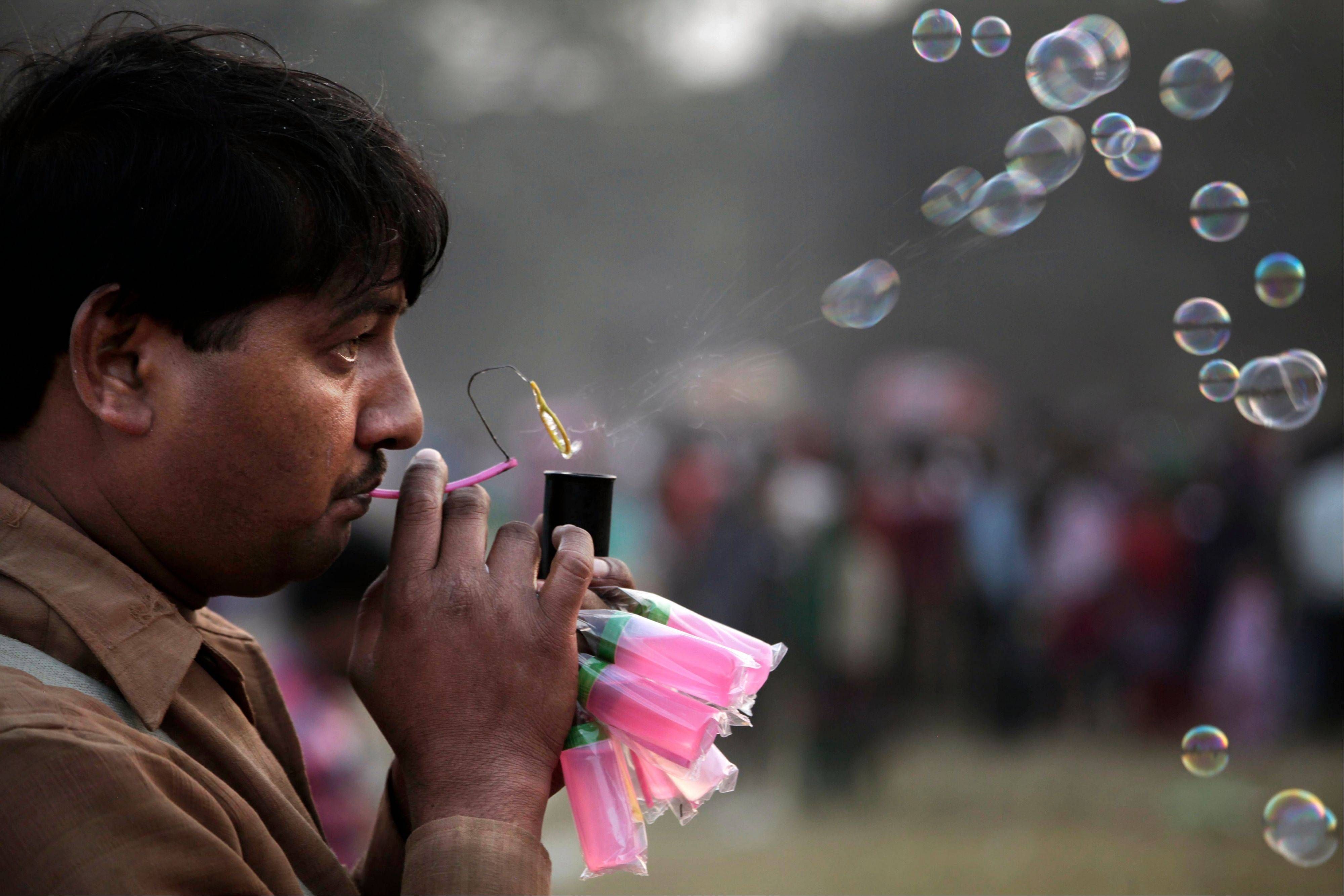 An Indian vendor blows soap bubbles to attract customers at a park in Kolkata, India, Wednesday, Jan. 1, 2014. Many people visited the public park on the first day of the New Year.