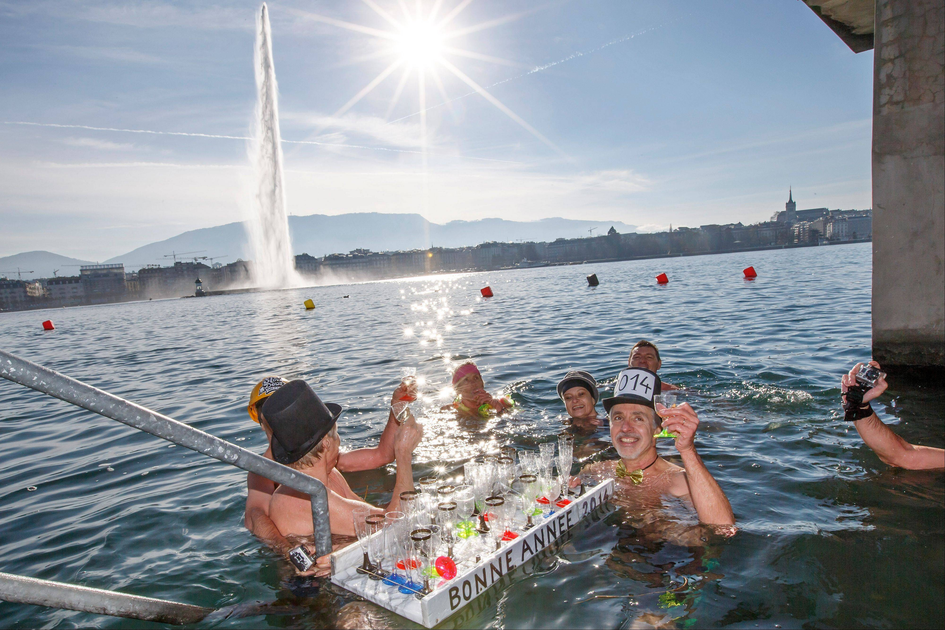 People toast with champagne while swimming in the cold water, during the annual swim in the Lake of Geneva for celebrating the New Year at the Bains des Paquis, in Geneva, Switzerland, Wednesday, Jan. 1, 2014.