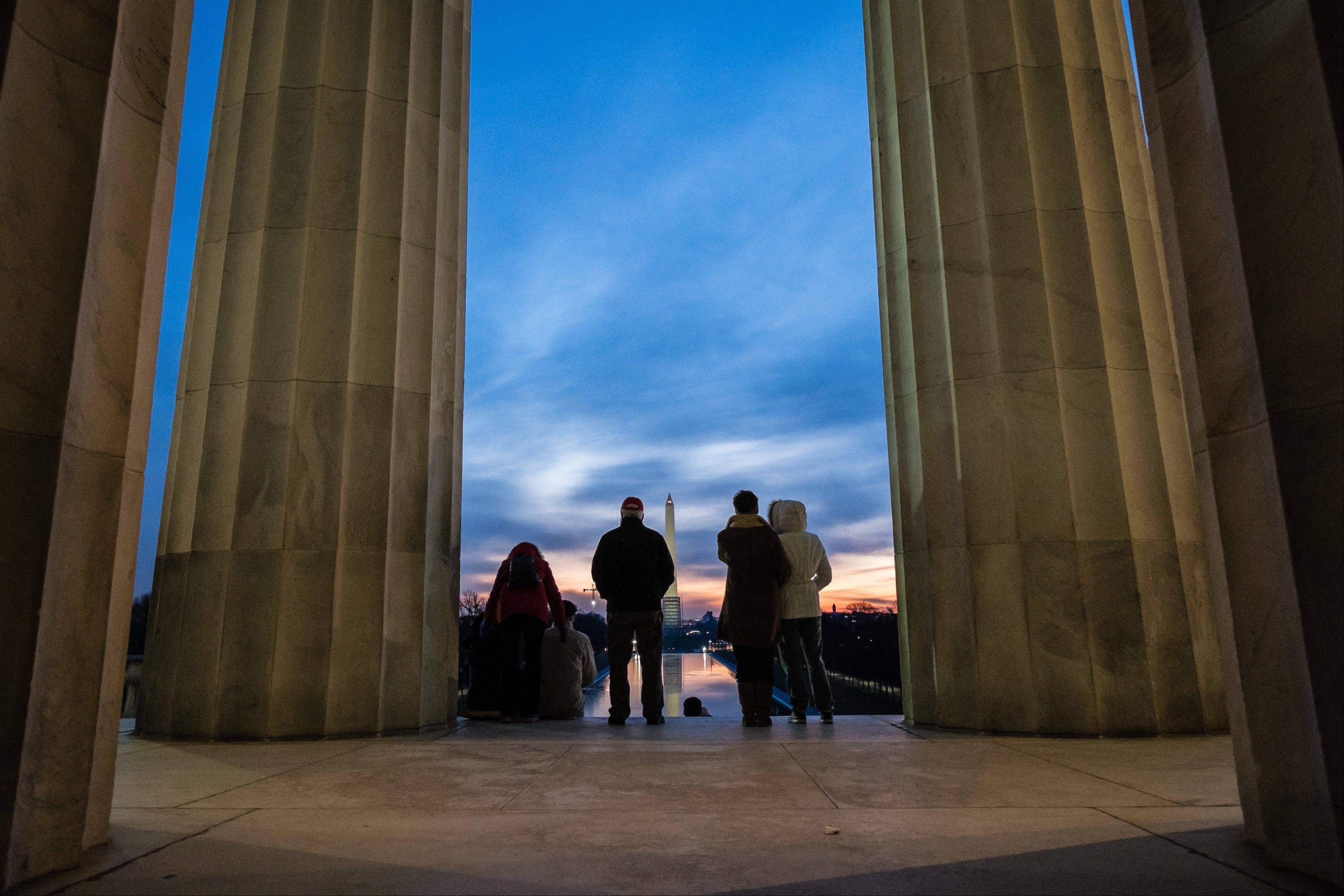 People gather at daybreak on the top steps of the Lincoln Memorial looking toward the Washington Monument to watch the first sunrise of the New Year in Washington, Wednesday, Jan. 1, 2014.
