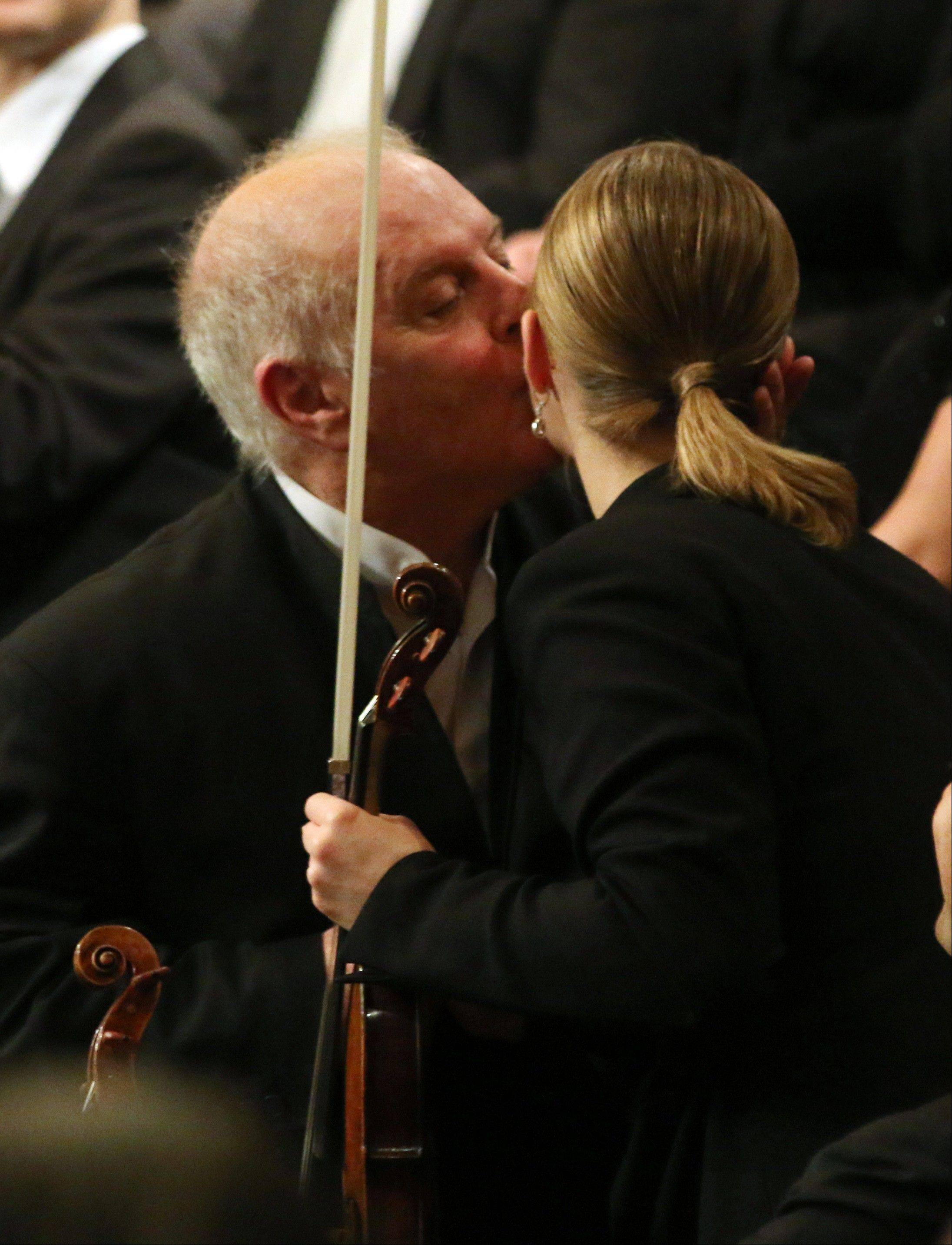 Argentine-born Maestro Daniel Barenboim kisses one of the musicians as he conducts the Vienna Philharmonic Orchestra during the traditional New Year's concert at the Golden Hall of the Musikverein in Vienna, Austria, Wednesday, Jan. 1, 2014.