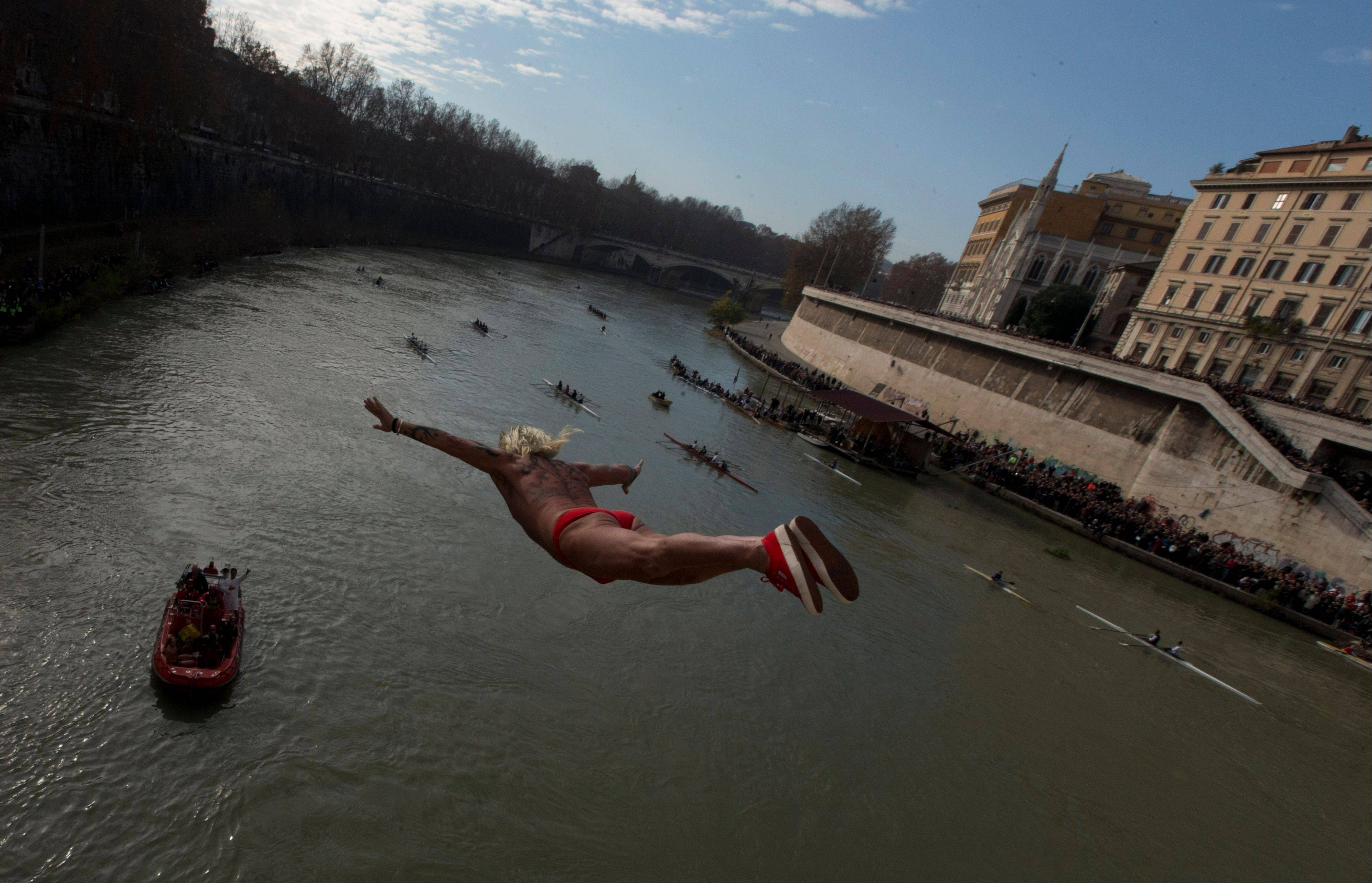 "Italy's Maurizio Palmulli known as ""Mister Ok"" dives into the Tiber River from the 18 meter (59 feet) high Cavour Bridge in Rome, Wednesday, Jan. 1, 2014, to celebrate the New Year."