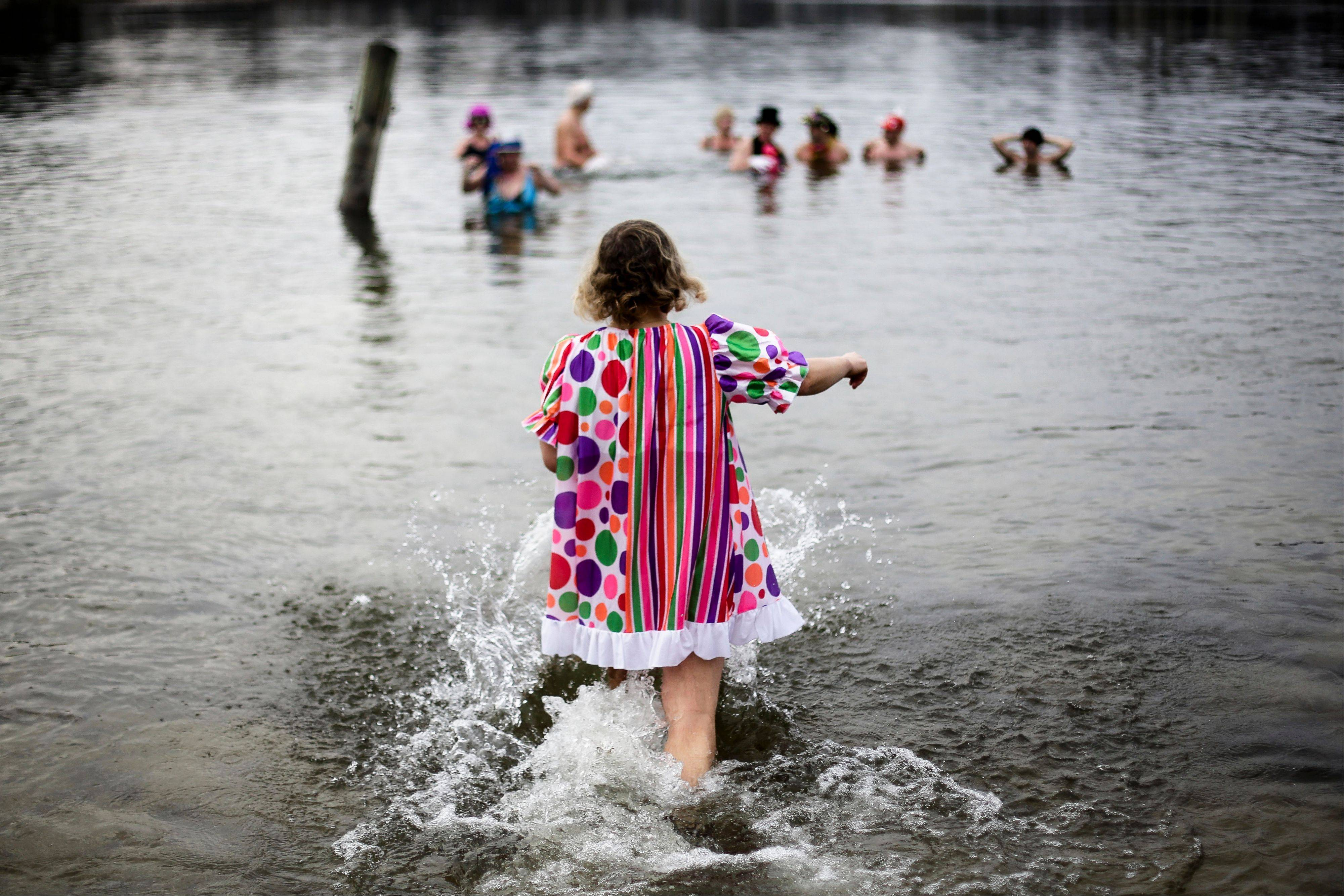 A woman with a colororful dress walks into the water as she attends the annual New Year's swimming of the winter swimming club Berliner Seehunde (Berlin Seals) at Oranke Lake in Berlin, Wednesday, Jan. 1, 2014.