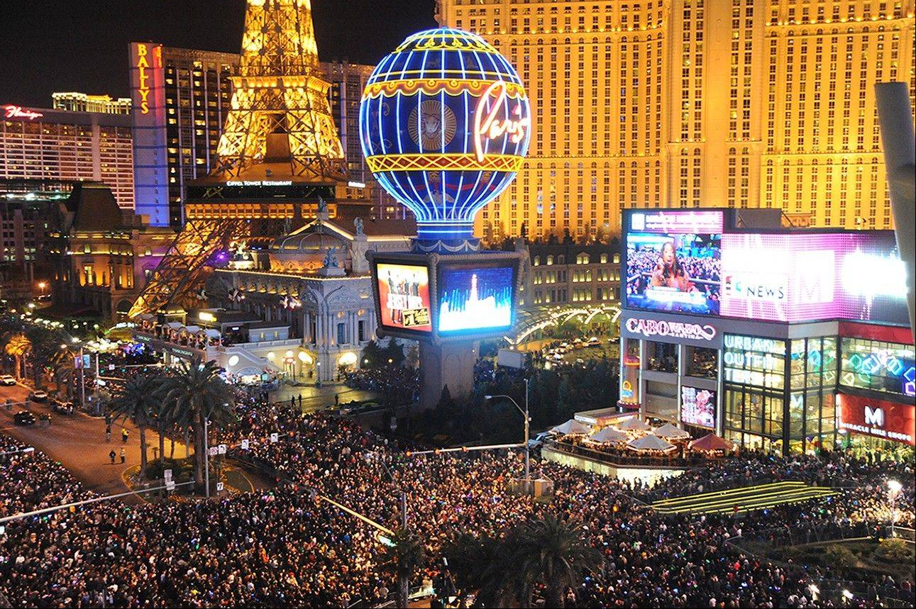 In this photo provided by the Las Vegas News Bureau, visitors crowd the Las Vegas Strip at midnight on Jan 1, 2014. Las Vegas officials expect to welcome approximately 335,000 visitors for the holiday.