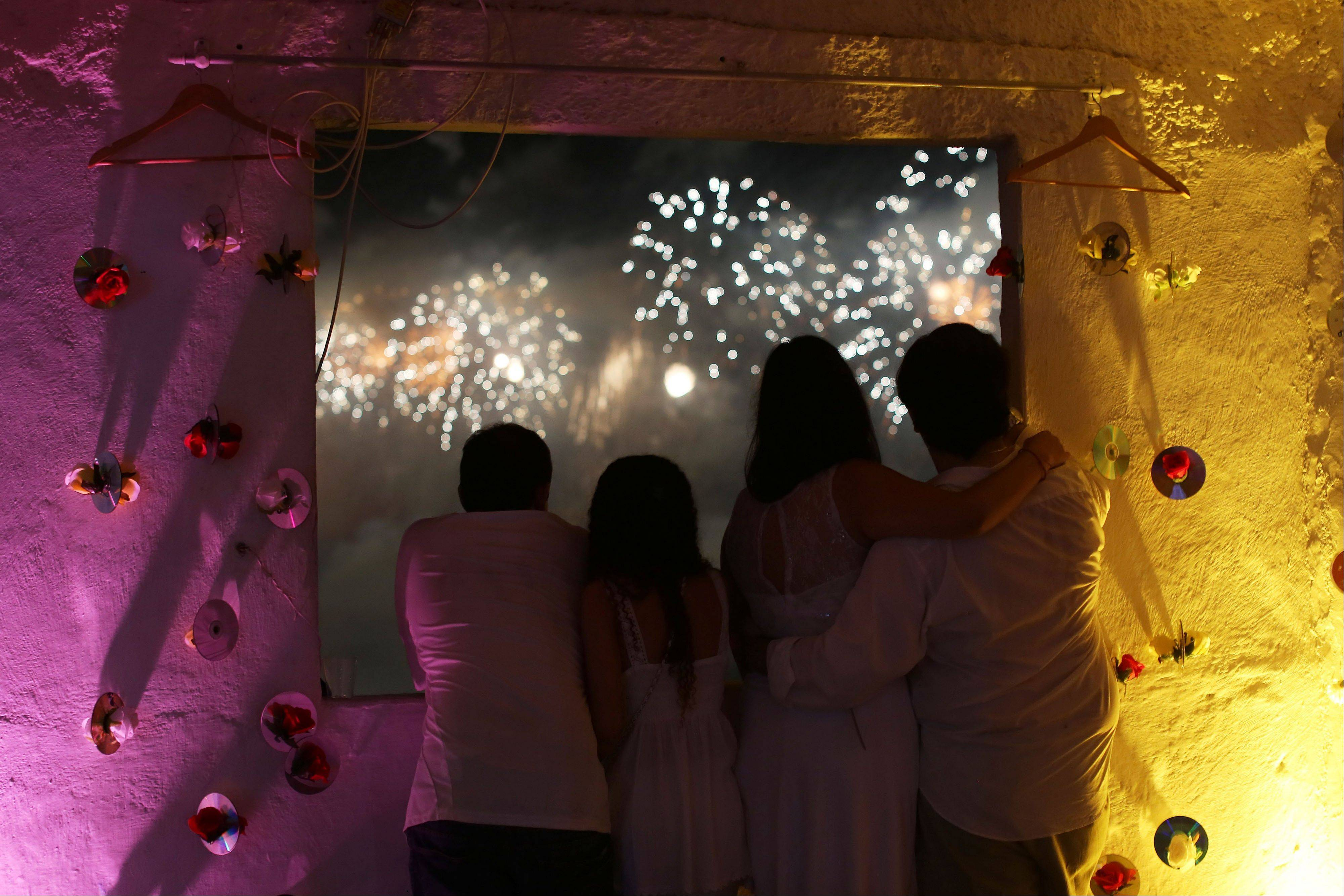 People on a rooftop in the Pavao Pavaozinho slum watch fireworks exploding over Copacabana beach during New Year's Eve celebrations in Rio de Janeiro, Brazil, Wednesday, Jan. 1, 2014.