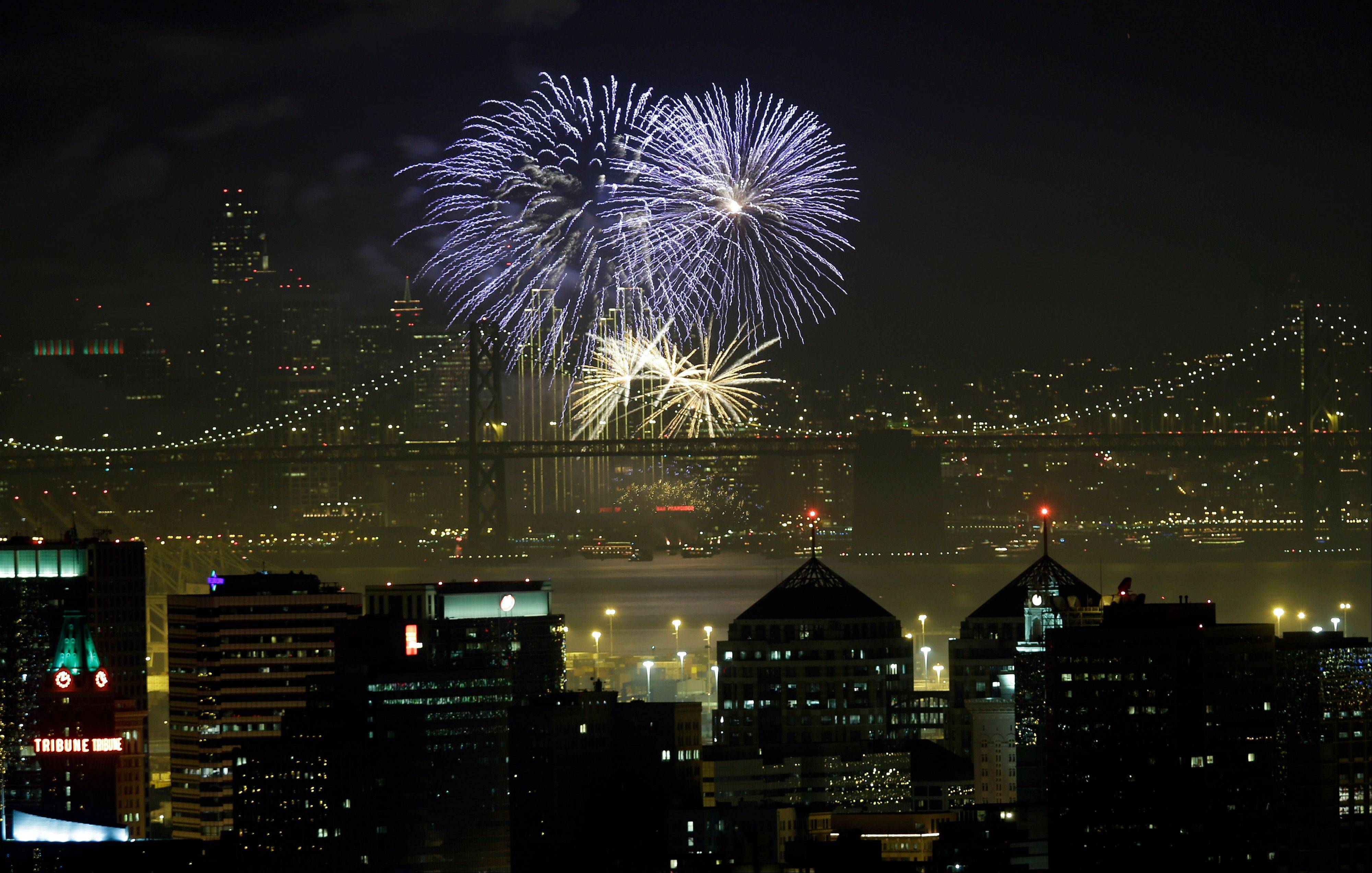 Fireworks fill the air in the bay over the Oakland, bottom, and San Francisco skylines, divided by the San Francisco Oakland Bay Bridge, as part of New Year's Eve celebrations in a view from Oakland, Calif. on Wednesday, Jan. 1, 2014.