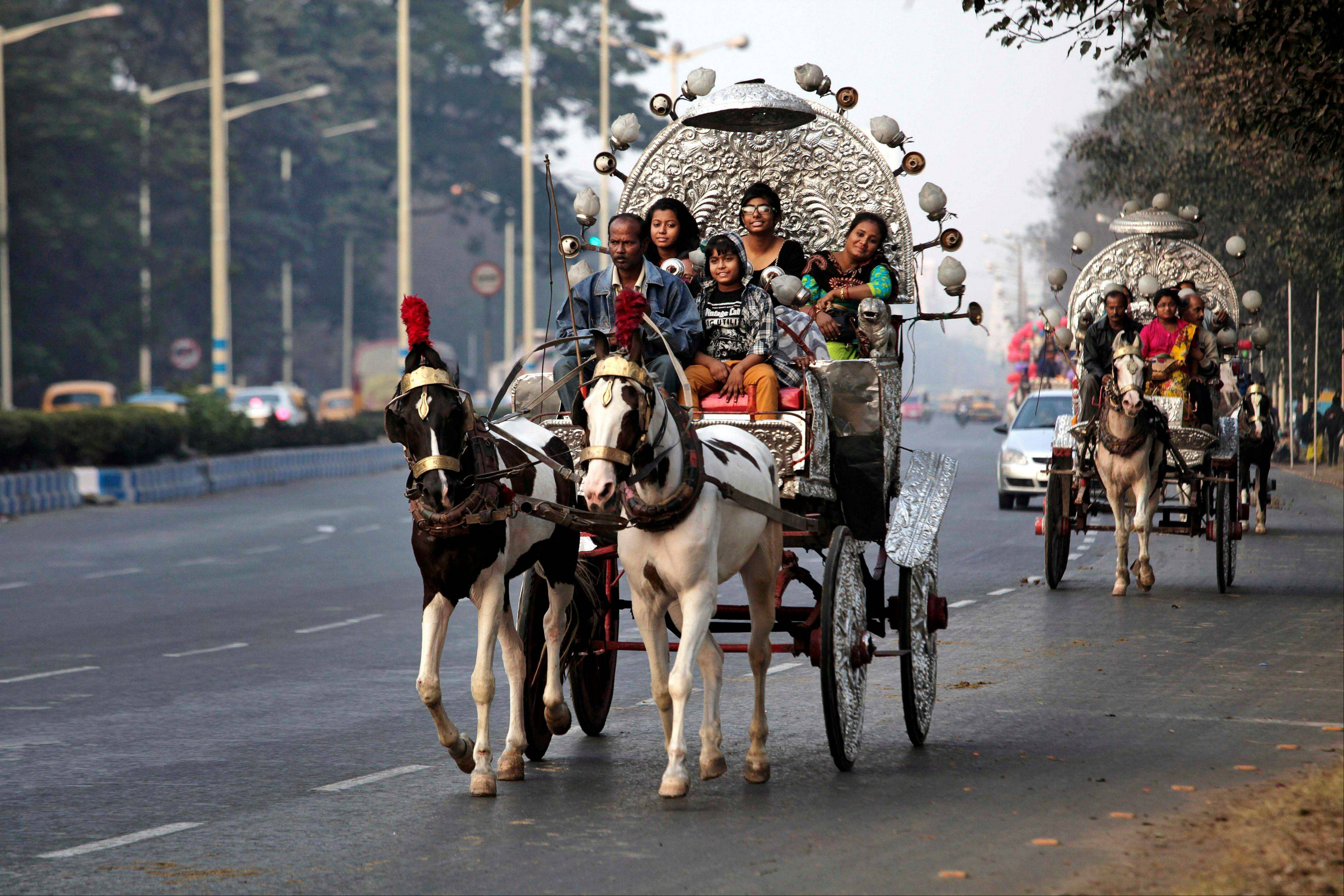 Indian families enjoy a ride on decorated horse driven carts on a street on the first day of the New Year, in Kolkata, India, Wednesday, Jan. 1, 2014.